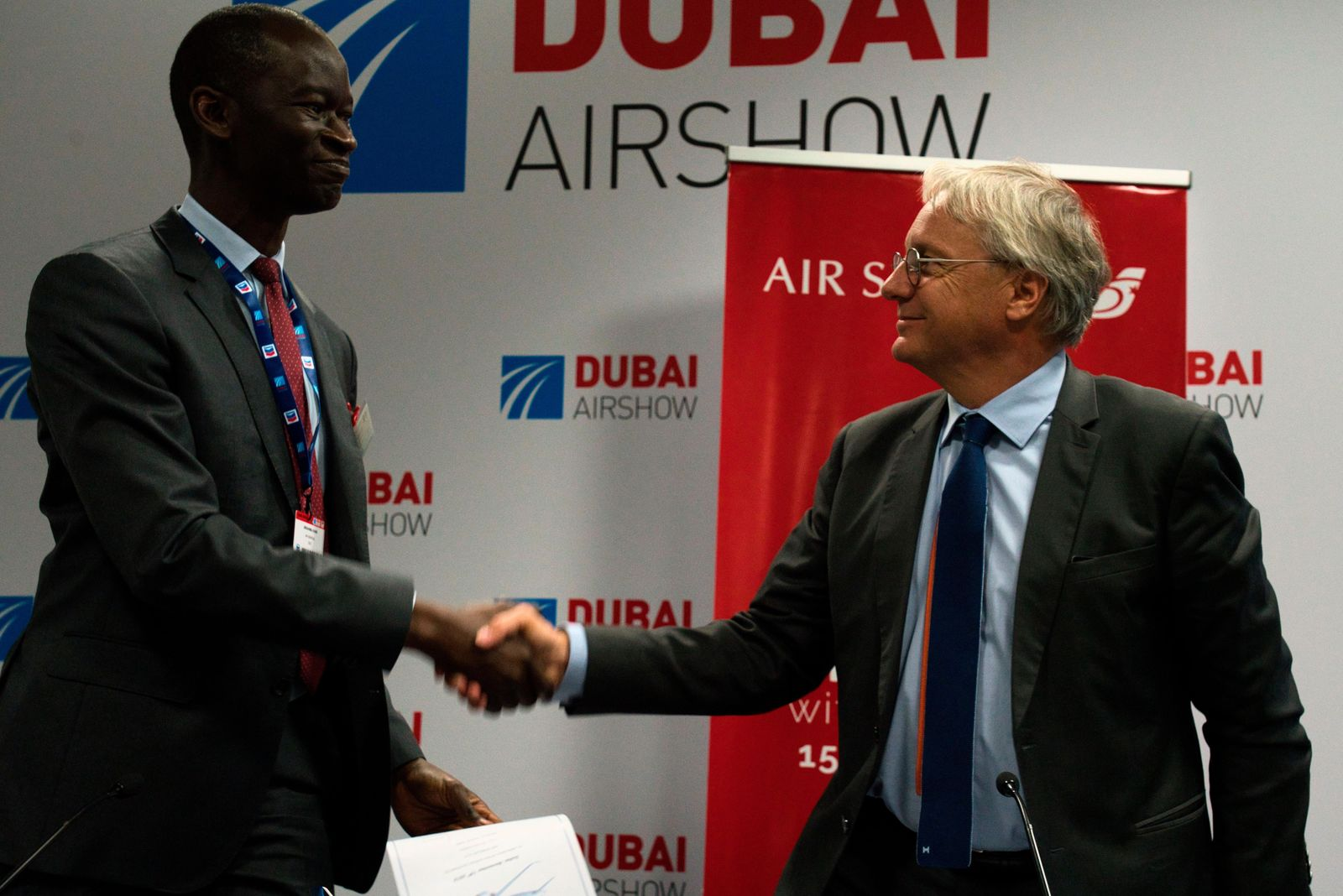 Air Senegal CEO Ibrahima Kane, left, shakes hands with Airbus' chief commercial officer Christian Scherer at a news conference at the Dubai Airshow in Dubai, United Arab Emirates, Tuesday, Nov. 19, 2019.. (AP Photo/Jon Gambrell)