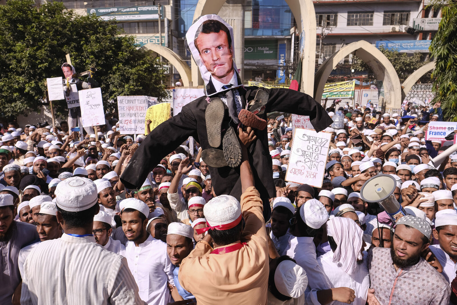 Supporters of Islamist parties carry an effigy of French President Emmanuel Macron during a protest after Friday prayers in Dhaka, Bangladesh, Friday, Oct. 30, 2020.(AP Photo/Mahmud Hossain Opu)