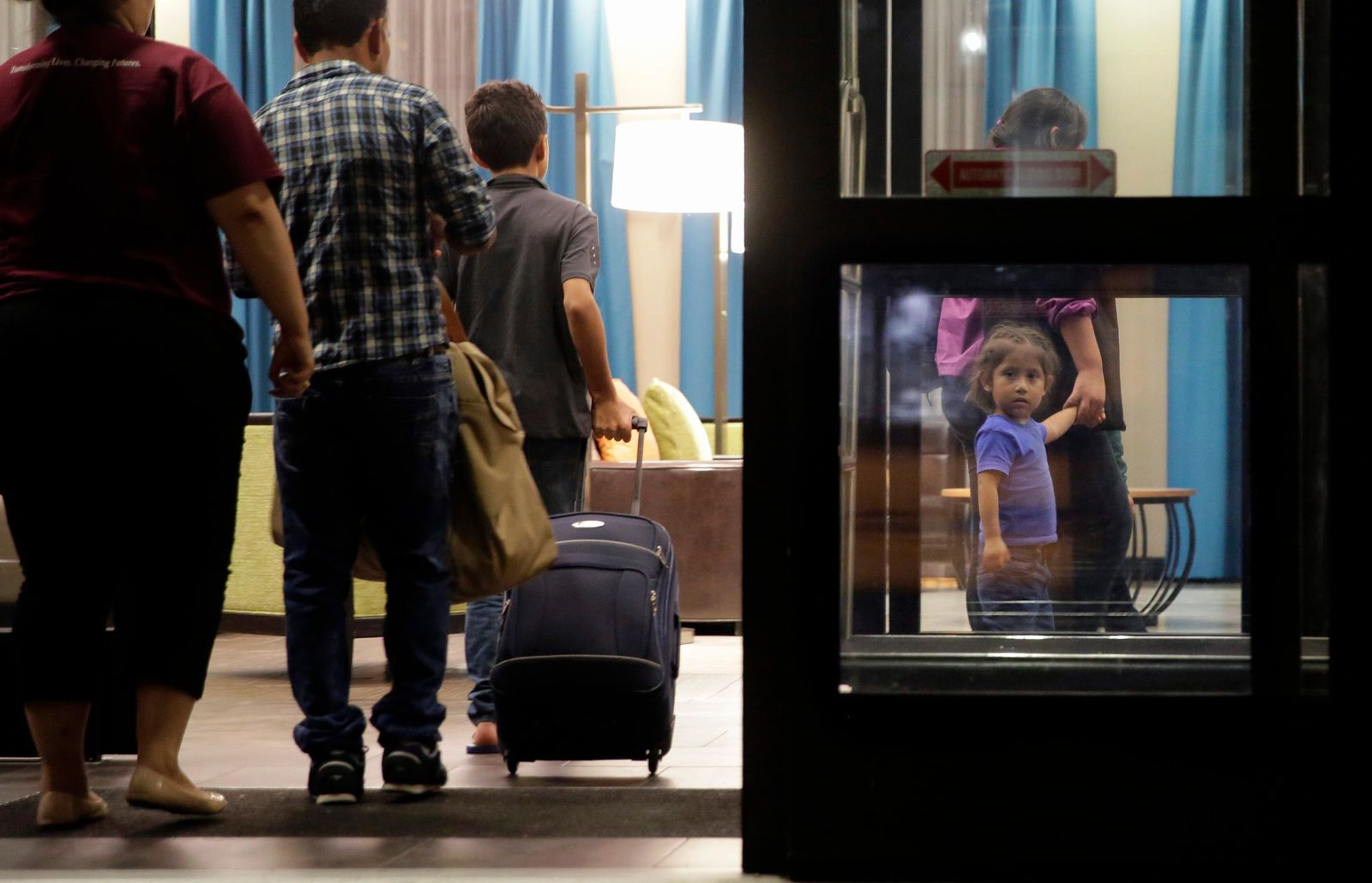 In this Monday, July 23, 2018, file photo, immigrants seeking asylum who were recently reunited arrive at a hotel, in San Antonio. (AP Photo/Eric Gay, File)