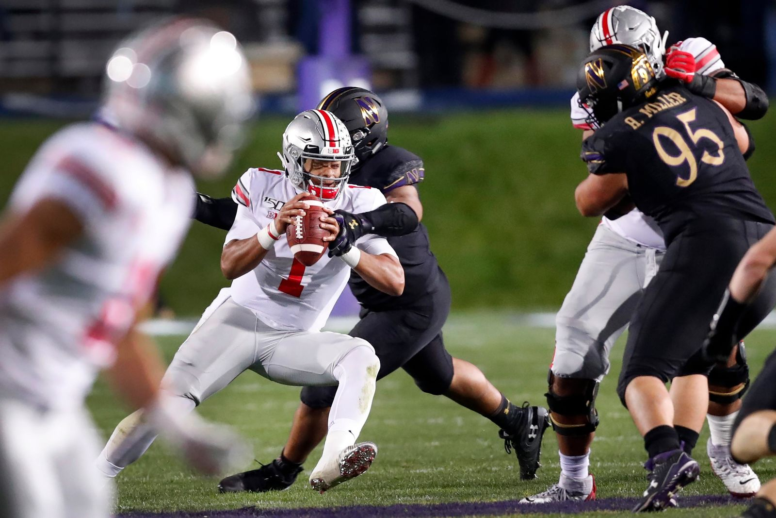 Ohio State quarterback Justin Fields (1) escapes pressure from Northwestern defensive end Earnest Brown IV during the first half of an NCAA college football game Friday, Oct. 18, 2019, in Evanston, Ill. (AP Photo/Charles Rex Arbogast)