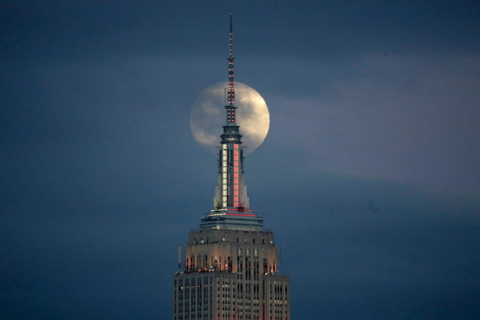 The moon is seen in its waxing gibbous stage as it rises behind the Empire State Building, Sunday, Jan. 20, 2019, seen from Jersey City, N.J. The moon will experience a lunar eclipse, when the earth moves directly between the sun and the moon, and will be seen across the United States late Sunday night. (AP Photo/Julio Cortez)