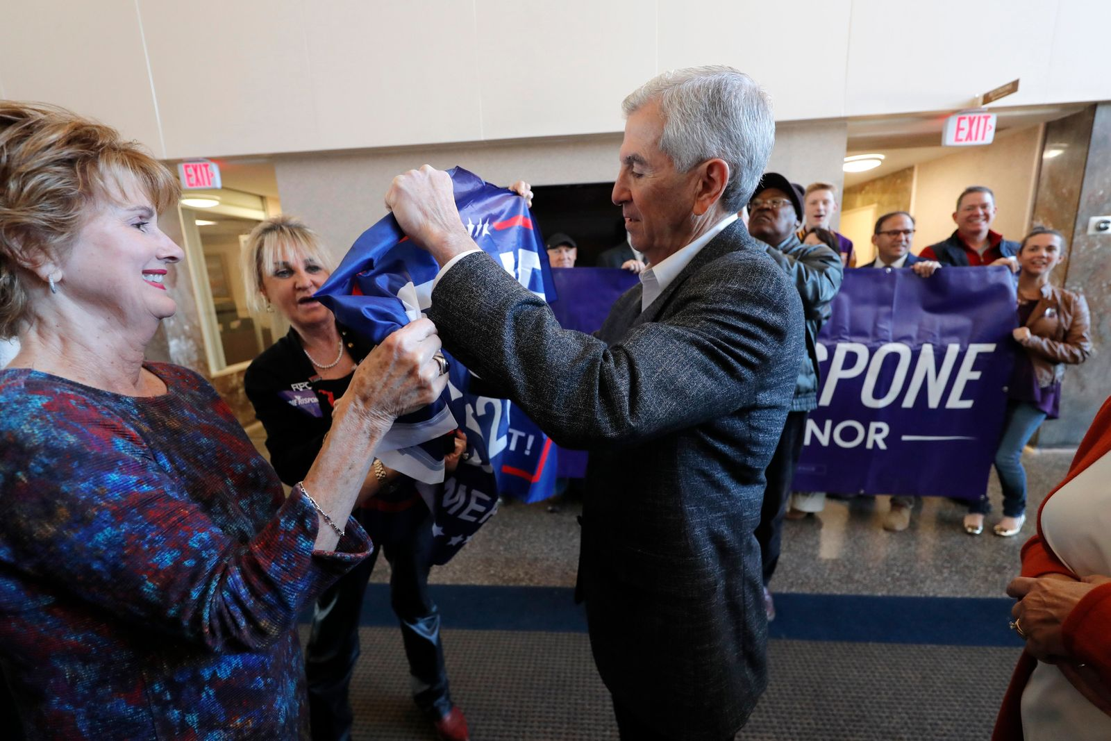 Louisiana Republican gubernatorial candidate Eddie Rispone signs a campaign banner as he greets supporters at a campaign stop in Shreveport, La., Friday, Nov. 15, 2019. (AP Photo/Gerald Herbert)