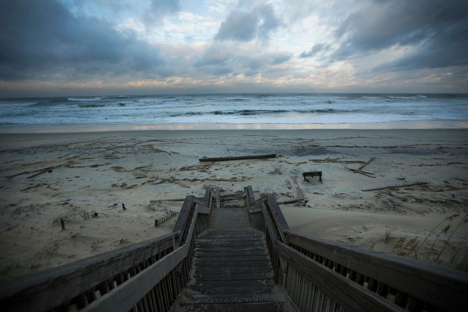 Wood debris is left scattered across the Nags Head beach in the Outer Banks, N.C., as the sunsets, Friday, Sept 6, 2019. Hurricane Dorian continues to churn off the North Carolina coast, but it's heading further into the Atlantic Ocean, prompting forecasters to lift hurricane and tropical storm warnings south of the Virginia-North Carolina border. (L. Todd Spencer/The Virginian-Pilot via AP)
