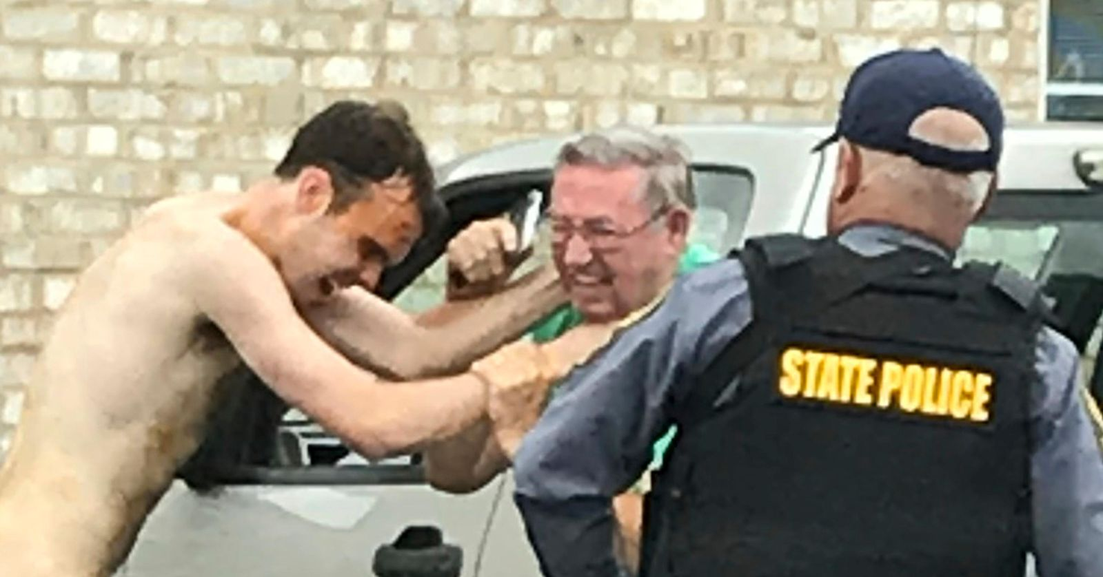 Matthew Thomas Bernard puts his hands on Keeling Baptist Church groundskeeper Loyd Gauldin, as a state police officer attempts to take him into custody on Tuesday, Aug. 27, 2019 in Keeling, Va. (Caleb Ayers/Danville Register & Bee via AP)