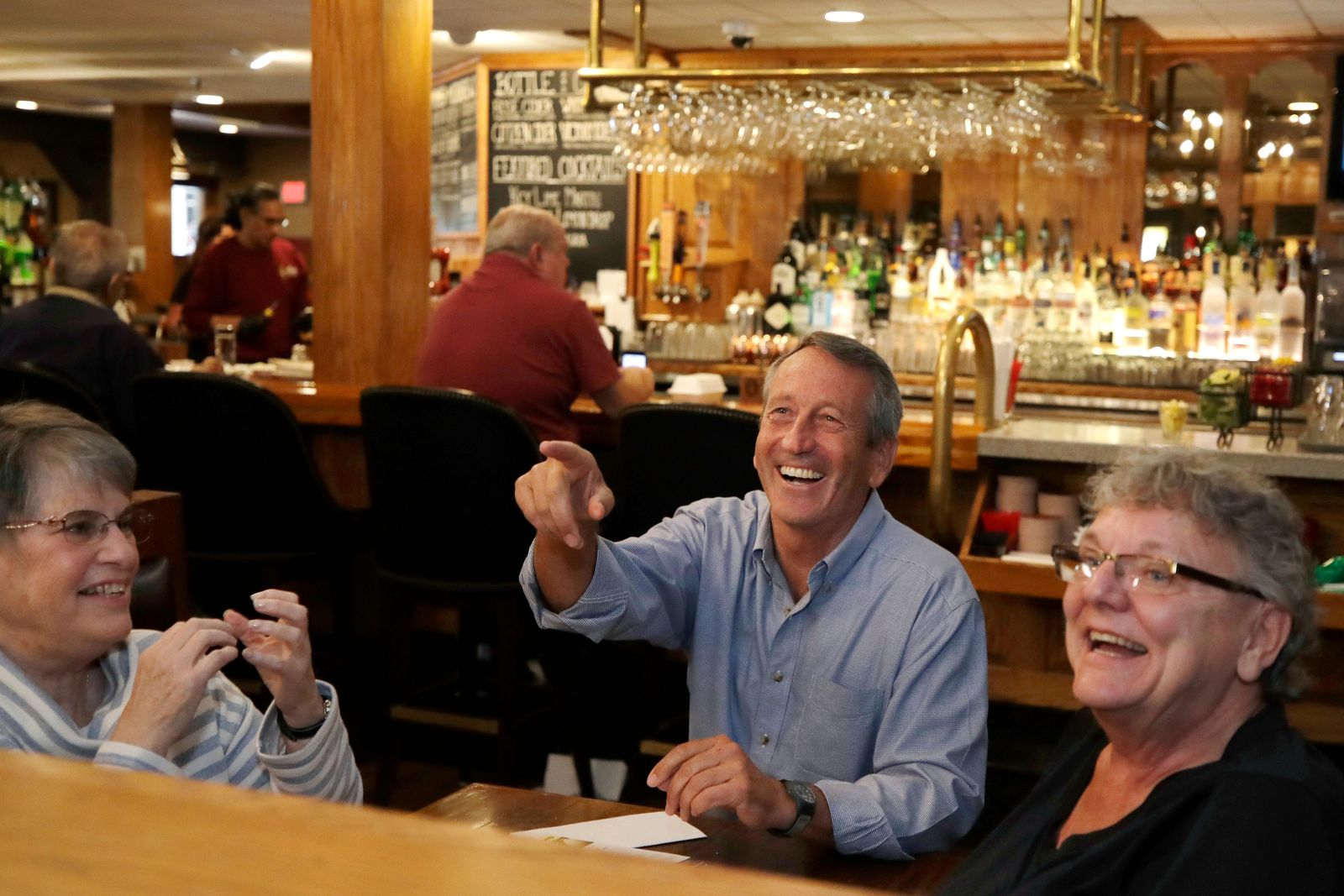 Republican presidential candidate, former South Carolina Gov. Mark Sanford chats with{ }patrons at the Puritan Backroom restaurant, as he campaigns, Thursday, Sept. 19, 2019, in Manchester, N.H. (AP Photo/Elise Amendola)