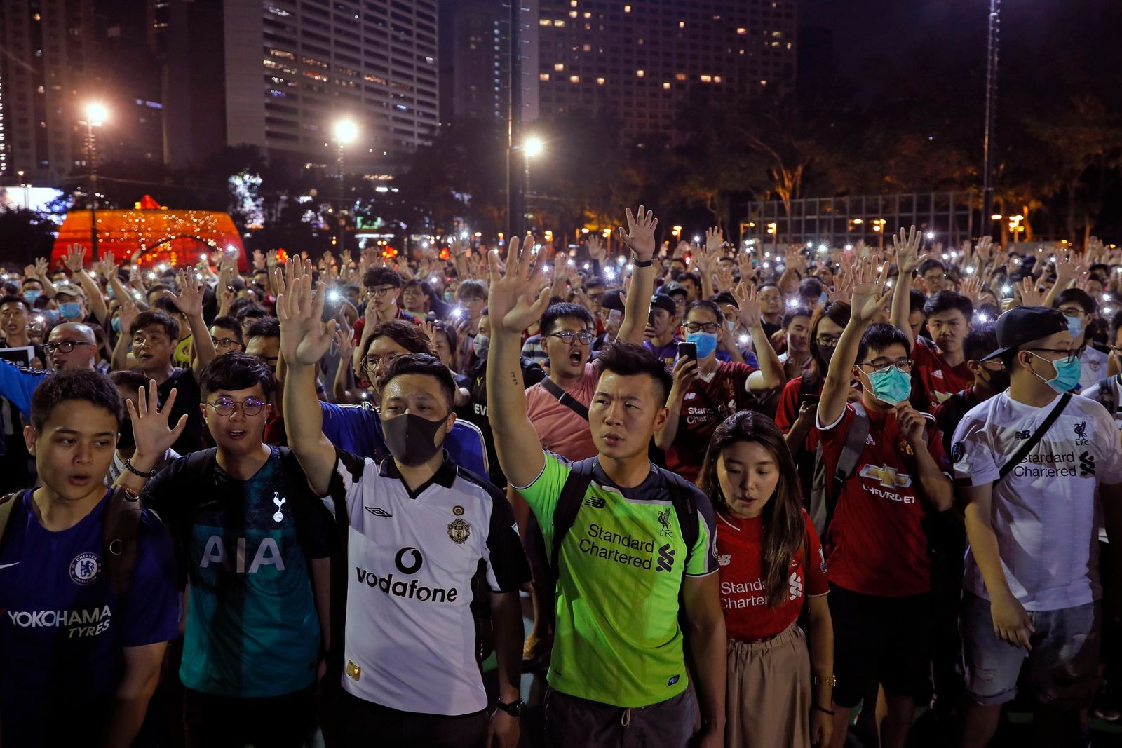 Pro-democracy football fans gather to form a human chain as they sing songs at