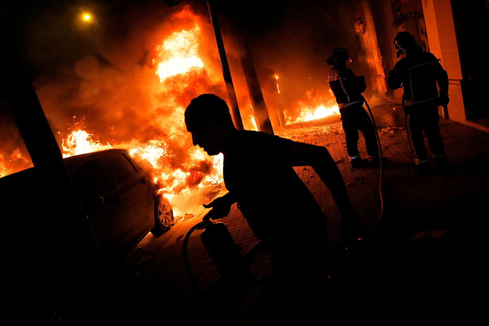Firefighters and residents try to put out fires burning cars during clashes between protestors and police in Barcelona, Spain, Wednesday, Oct. 16, 2019.{ } (AP Photo/Bernat Armangue)