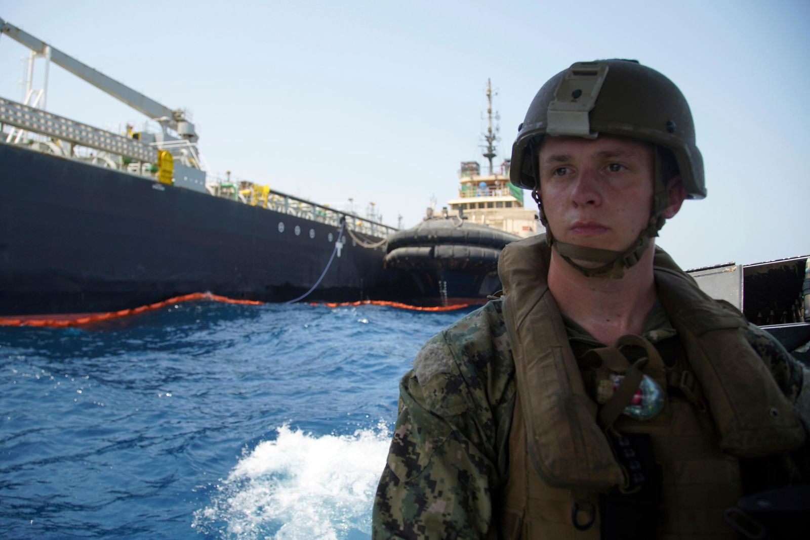 The damaged Panama-flagged, Japanese owned oil tanker Kokuka Courageous, that the U.S. Navy says was damaged by a limpet mine, is seen behind a U.S. sailor, during a trip organized by the Navy for journalists, off Fujairah, United Arab Emirates, Wednesday, June 19, 2019.{ } (AP Photo/Fay Abuelgasim)
