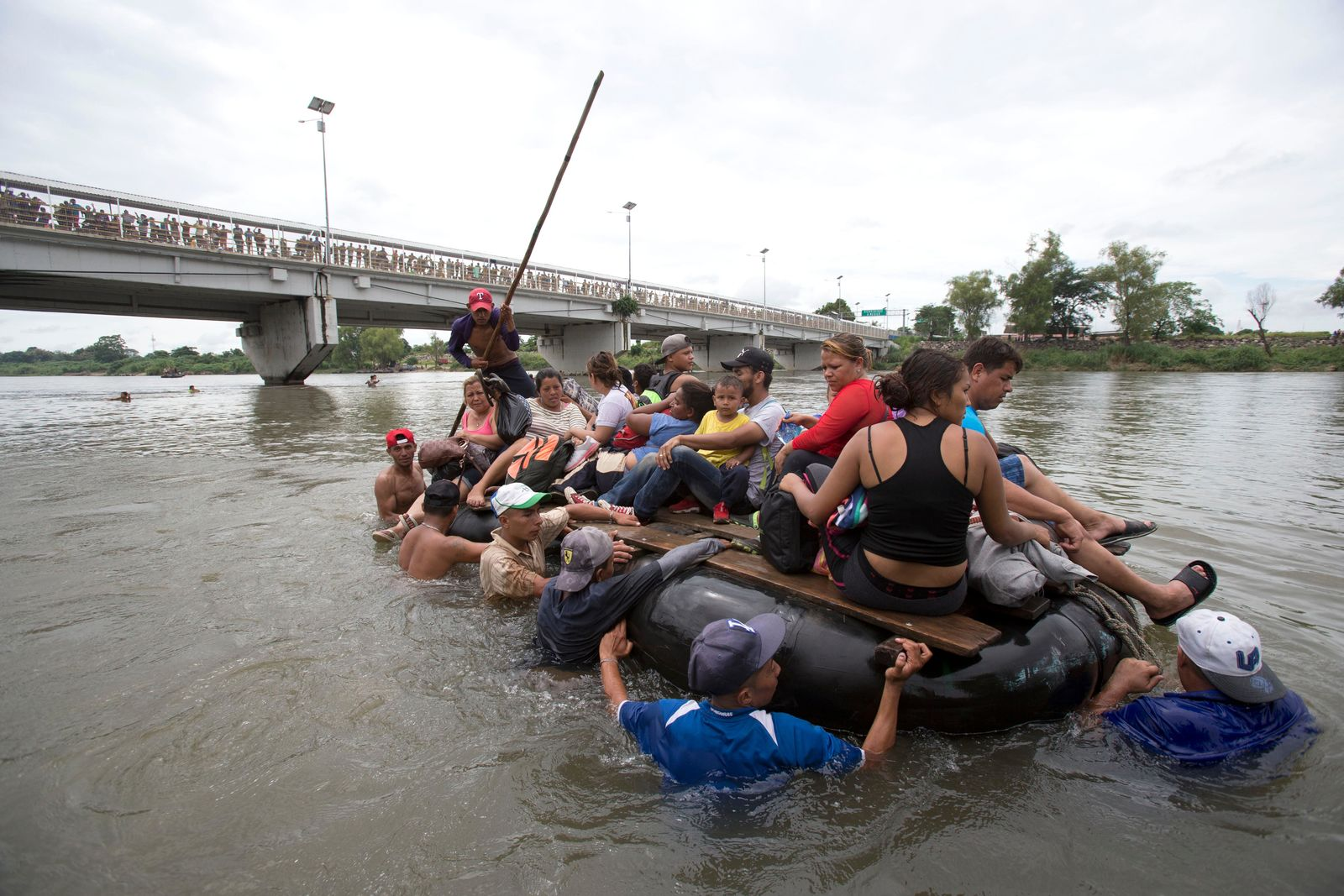 A group of Central American migrants cross the Suchiate River aboard a raft made out of tractor inner tubes and wooden planks, on the the border between Guatemala and Mexico, in Ciudad Hidalgo, Mexico, Saturday, Oct. 20, 2018. (AP Photo/Moises Castillo)
