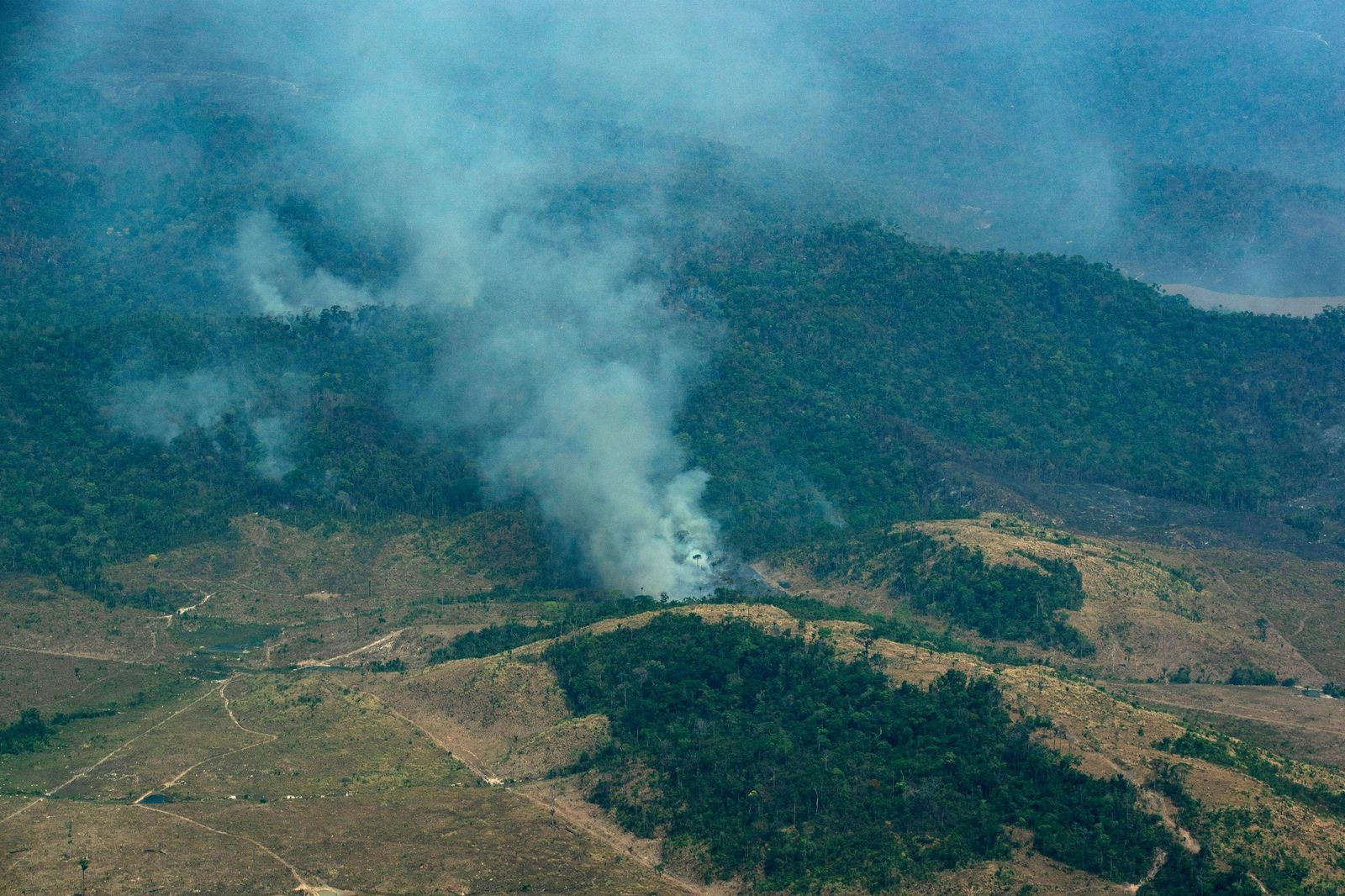 Smoke rises from a rainforest in Altamira, Para state, Brazil, Wednesday, Aug. 28, 2019. Brazilian President Jair Bolsonaro said Wednesday that Latin America's Amazon countries will meet in September to discuss both protecting and developing the rainforest region, which has been hit by weeks of devastating fires.(AP Photo/Leo Correa)