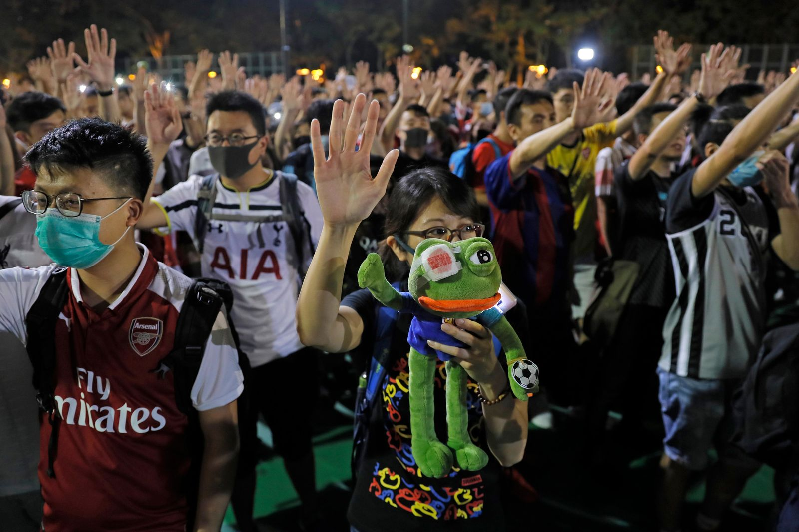 A pro-democracy football fan shows a frog toy as she forms part of a human chain at Victoria Park in Hong Kong, Wednesday, Sept. 18, 2019. . (AP Photo/Kin Cheung)
