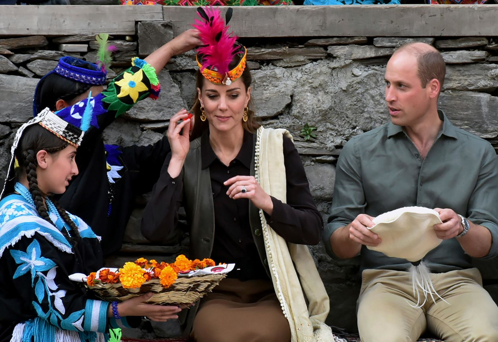 In this photo released by Press Information Department, Mmembers of Kalash community greet Britain's Prince William, center, and his wife Kate with traditional caps during their visit to Bumburate Valley, an area of Pakistan's northern Chitral district, Wednesday Oct. 16, 2019. (Press Information Department via AP)