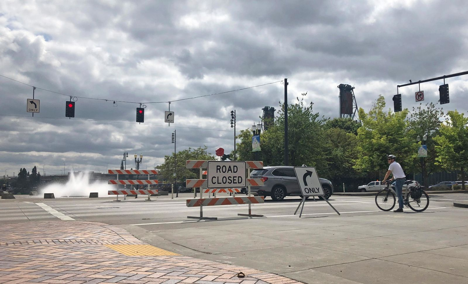 A bicyclist stands by a road closure sign put up in advance of a large rally as the city prepares for crowds in Portland, Ore., Friday, Aug. 16, 2019. In the past week, authorities in Portland have arrested a half-dozen members of right-wing groups on charges related to violence at previous politically motivated rallies as the liberal city braces for potential clashes between far-right groups and self-described anti-fascists who violently oppose them. (AP Photo/Gillian Flaccus)