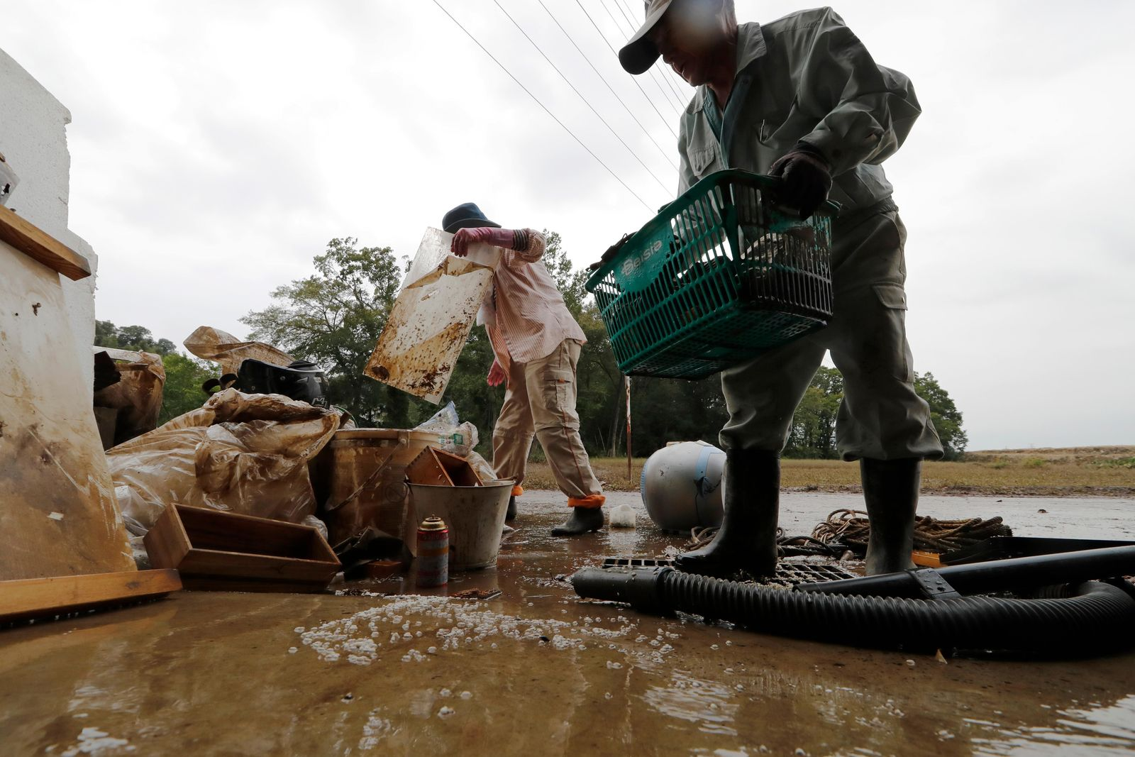 Residents Kazuo Saito, right, and Sumiko Saito clean up their home Monday, Oct. 14, 2019, in Kawagoe City, Japan. Typhoon Hagibis dropped record amounts of rain for a period in some spots, according to meteorological officials, causing more than 20 rivers to overflow. (AP Photo/Eugene Hoshiko)