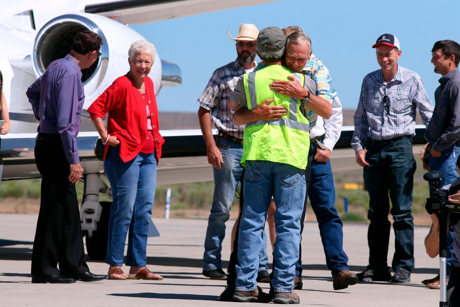 Rancher Dwight Hammond Jr., center, is embraced after arriving by private jet at the Burns Municipal Airport, Wednesday, July 11, 2018, in Burns, Ore. Hammond and his son Steven, convicted of intentionally setting fires on public land in Oregon, were pardoned by President Donald Trump on Tuesday, July 10. (Beth Nakamura/The Oregonian via AP)