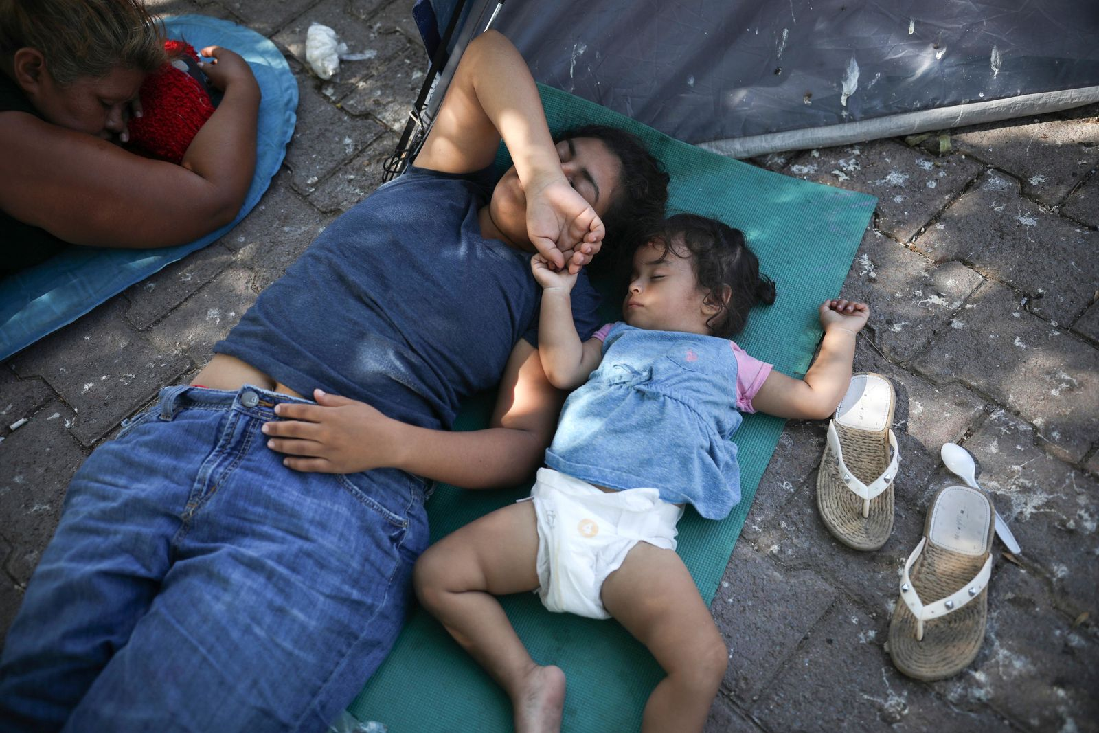 In this Aug. 1, 2019, photo, migrants rest near a Mexican immigration center where migrants set up camp in Matamoros, Mexico.{ } (AP Photo/Emilio Espejel)