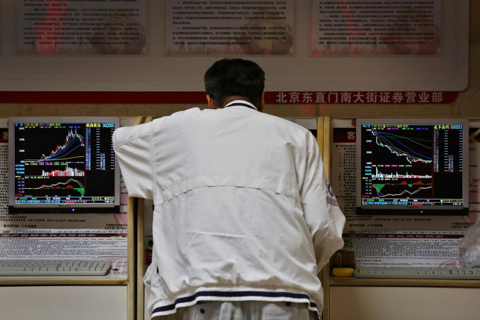 A man checks stock prices at a brokerage house in Beijing, Monday, May 13, 2019. Shares were mostly lower in Asia on Monday after trade talks between the U.S. and China ended Friday without an agreement. (AP Photo/Andy Wong)