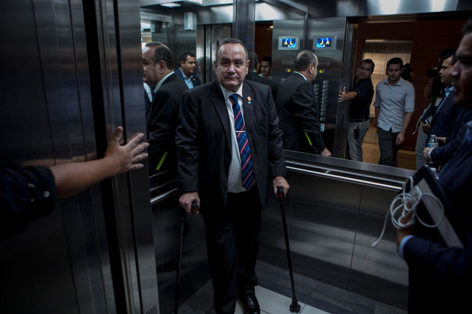 Guatemala's President-elect Alejandro Giammattei stands in an elevator as he arrives for an interview in Guatemala City, Tuesday, Aug. 13, 2019.{ } (AP Photo/Oliver de Ros)
