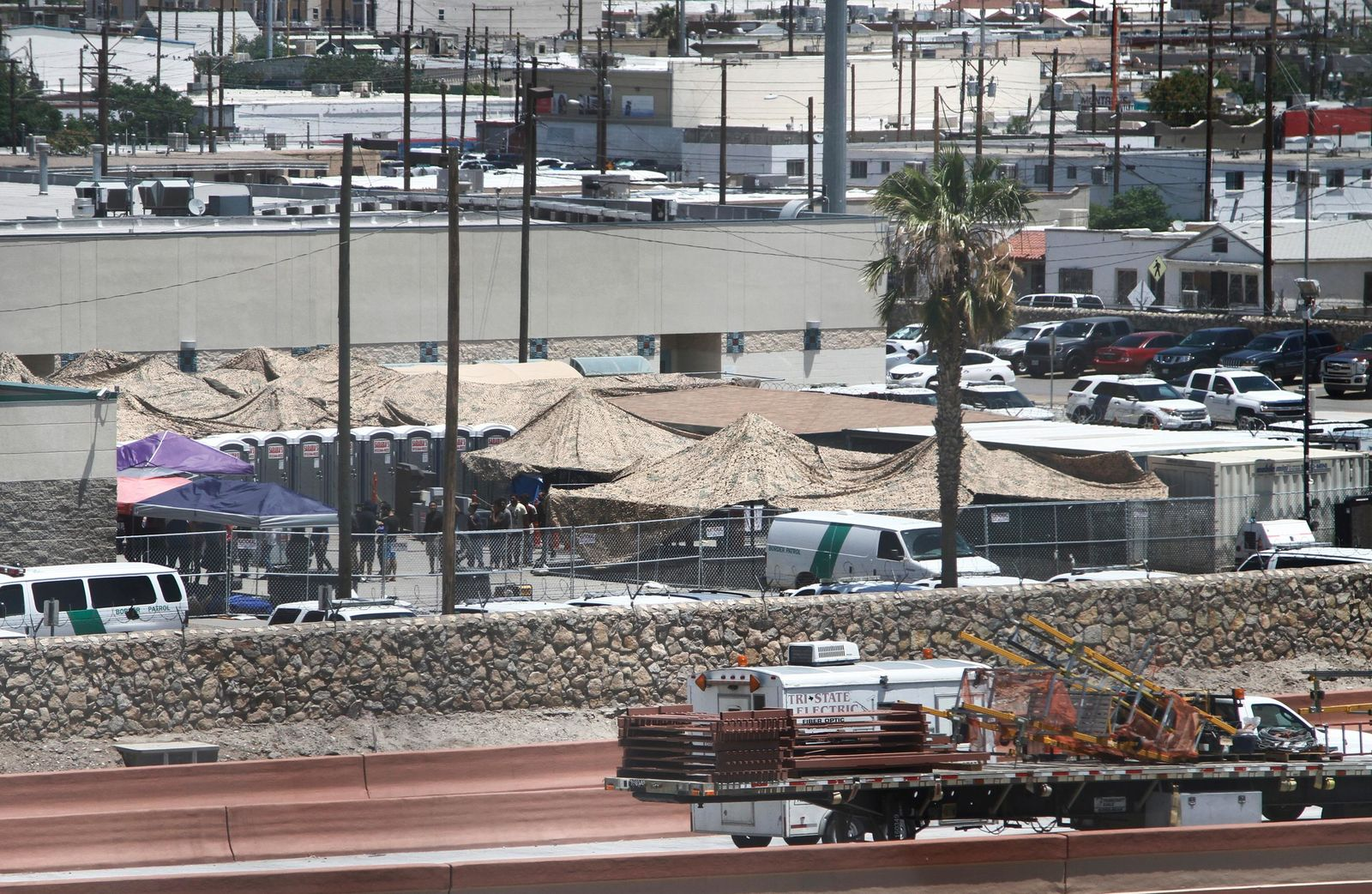 In this June 12, 2019 ,photo, migrants are seen within a fenced-off area inside a temporary outdoor encampment where they're waiting to be processed in El Paso, Texas.{ } (AP Photo/Cedar Attanasio)