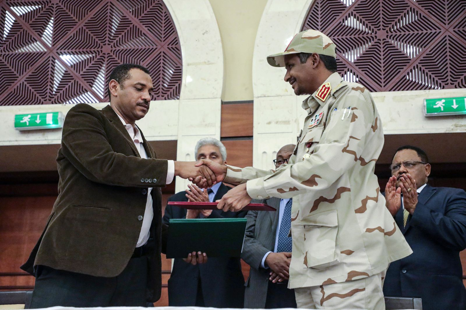 Gen. Mohammed Hamdan Dagalo, right, and Sudan's pro-democracy movement leader Ahmad al-Rabiah shake hands after signing a power sharing document in Khartoum, Sudan, Wednesday, July 17, 2019.{ } (AP Photo/Mahmoud Hjaj)