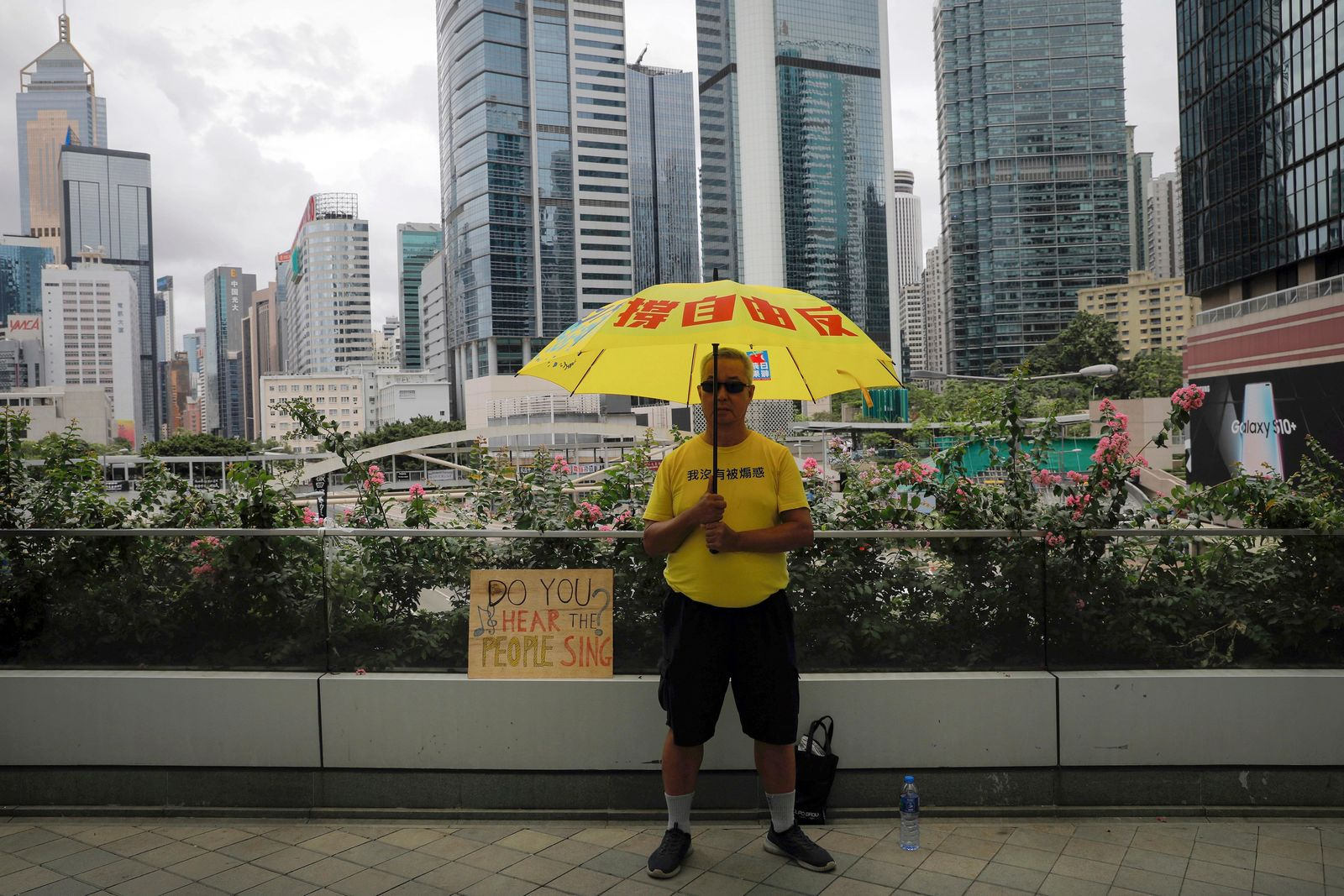 A man holds an umbrella outside the Legislative Council following last weekend's massive protest against the unpopular extradition bill in Hong Kong, Tuesday, June 18, 2019. Hong Kong's government headquarters reopened Tuesday as the number of protesters outside dwindled to a few dozen and life returned to normal in the former British colony. (AP Photo/Vincent Yu)