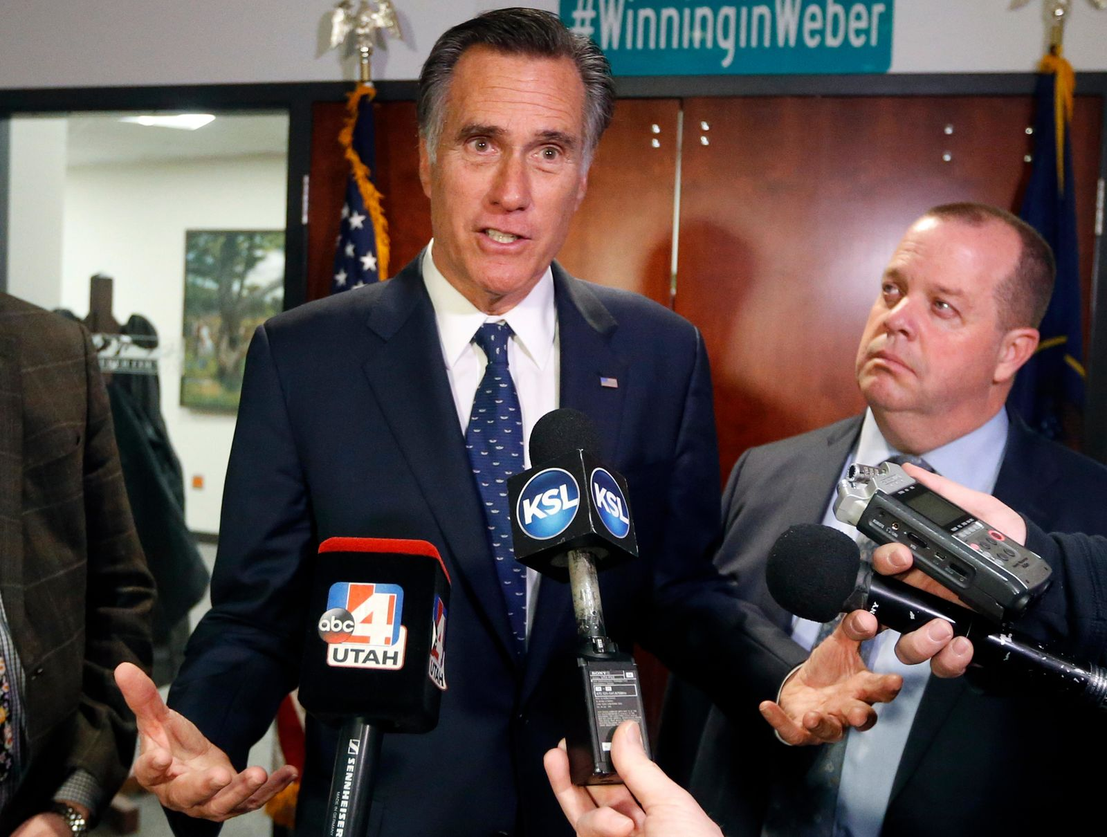 Utah Sen. Mitt Romney, left, speaks with reporters after visiting with local officials to discuss how the four-week partial government shutdown is impacting an area with several major federal employers, including the Internal Revenue Service, Friday Jan., 18, 2019, in Ogden, Utah. (AP Photo/Rick Bowmer)