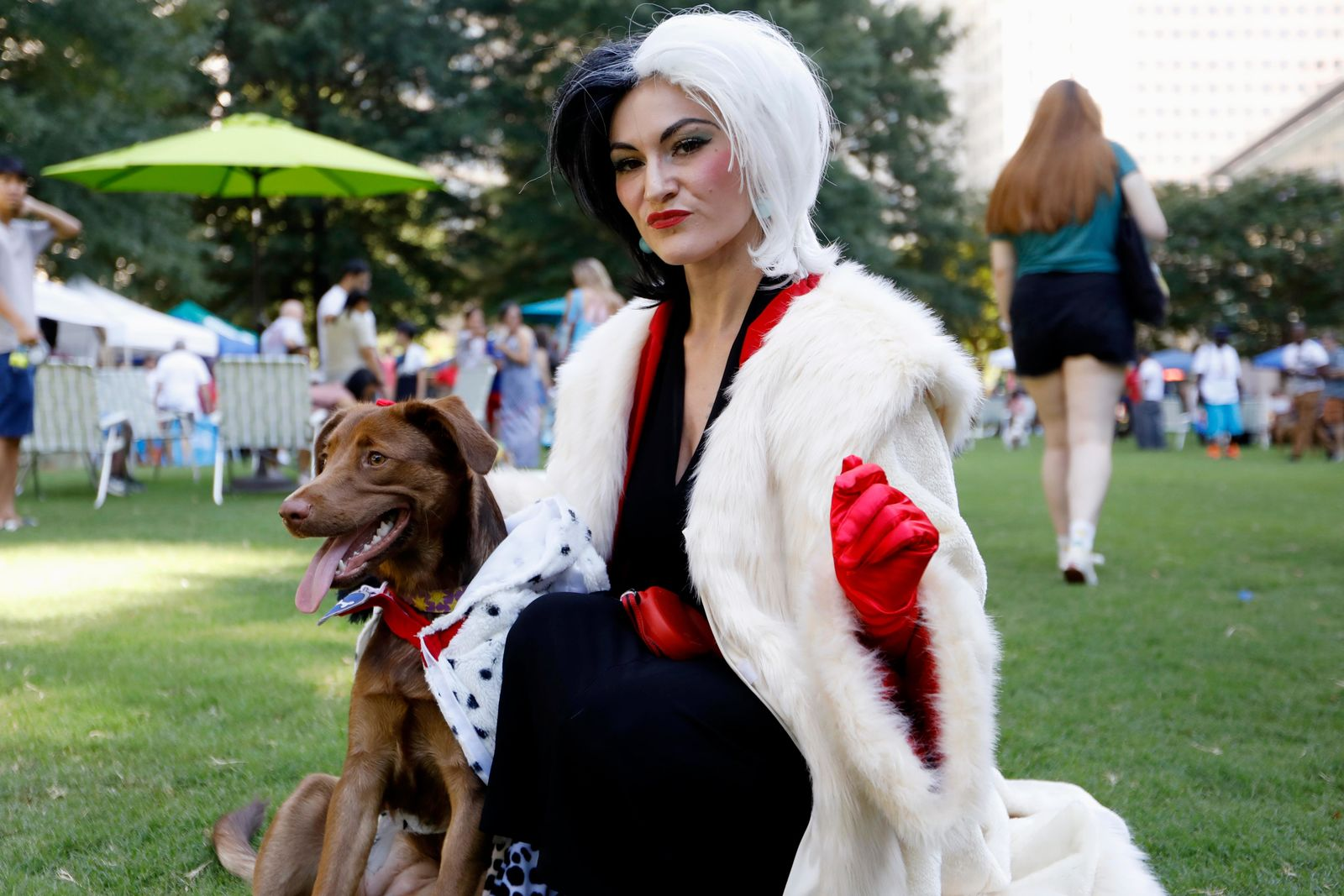 Atlanta-area resident Megan Nelson poses for a photo with her dog Darla during Doggy Con in Woodruff Park, Saturday, Aug. 17, 2019, in Atlanta. Nelson wore a Cruella de Vil costume and dressed her mixed chocolate Labrador Retriever in a Dalmatian outfit. The pair won the costume contest award for best dog and owner combination. (AP Photo/Andrea Smith)