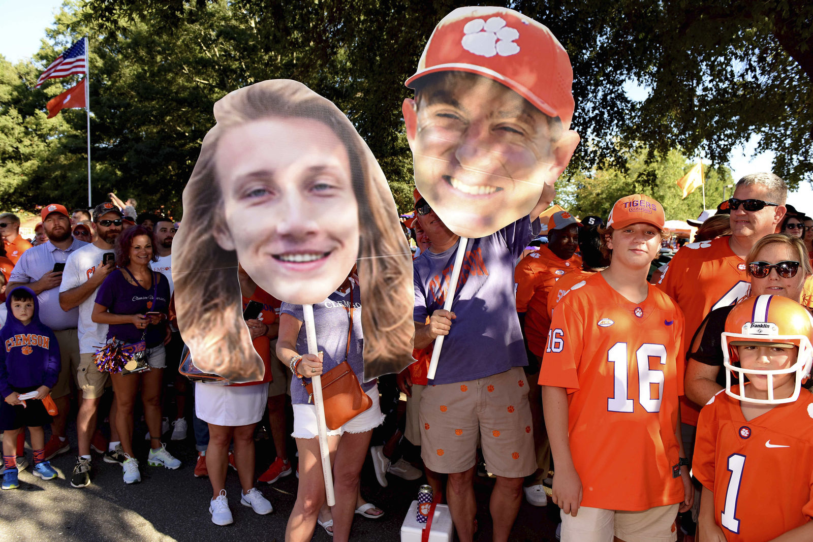 Clemson fans hold large images of Trevor Lawrence, left, and coach Dabo Swinney during the Tiger Walk before the team's NCAA college football game against Georgia Tech on Thursday, Aug. 29, 2019, in Clemson, S.C. (AP Photo/Richard Shiro)