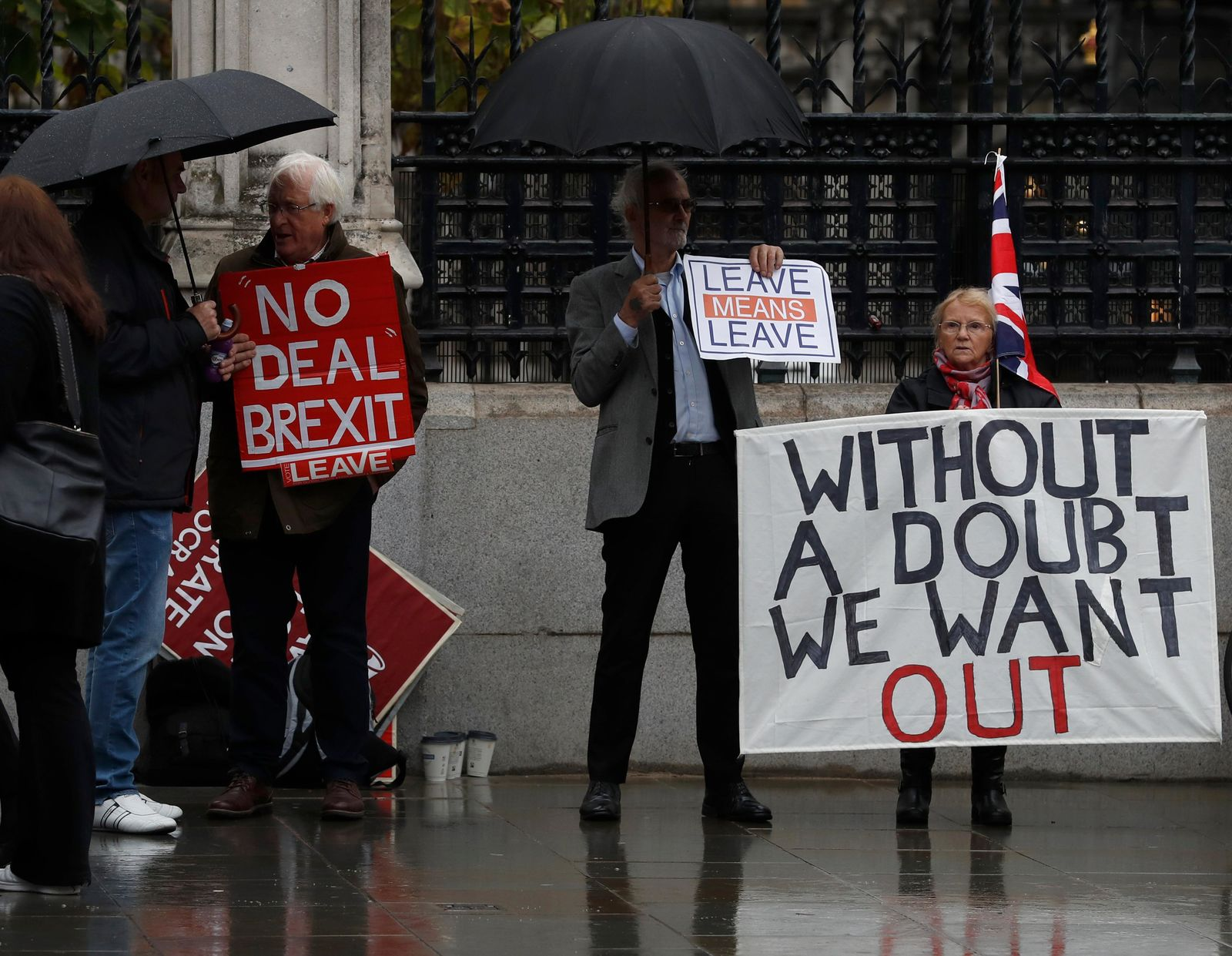 Pro-Brexit campaigners stand under umbrellas with their placards outside the Houses of Parliament in London, Monday, Oct. 21, 2019. (AP Photo/Alastair Grant)