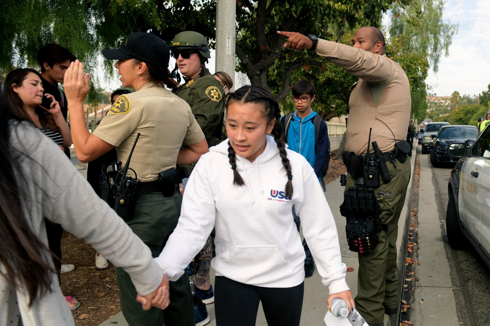 Students evacuate their campus after a gunman opened fire at Saugus High School on Thursday, Nov. 14, 2019, in Santa Clarita, Calif. (AP Photo/Christian Monterrosa)