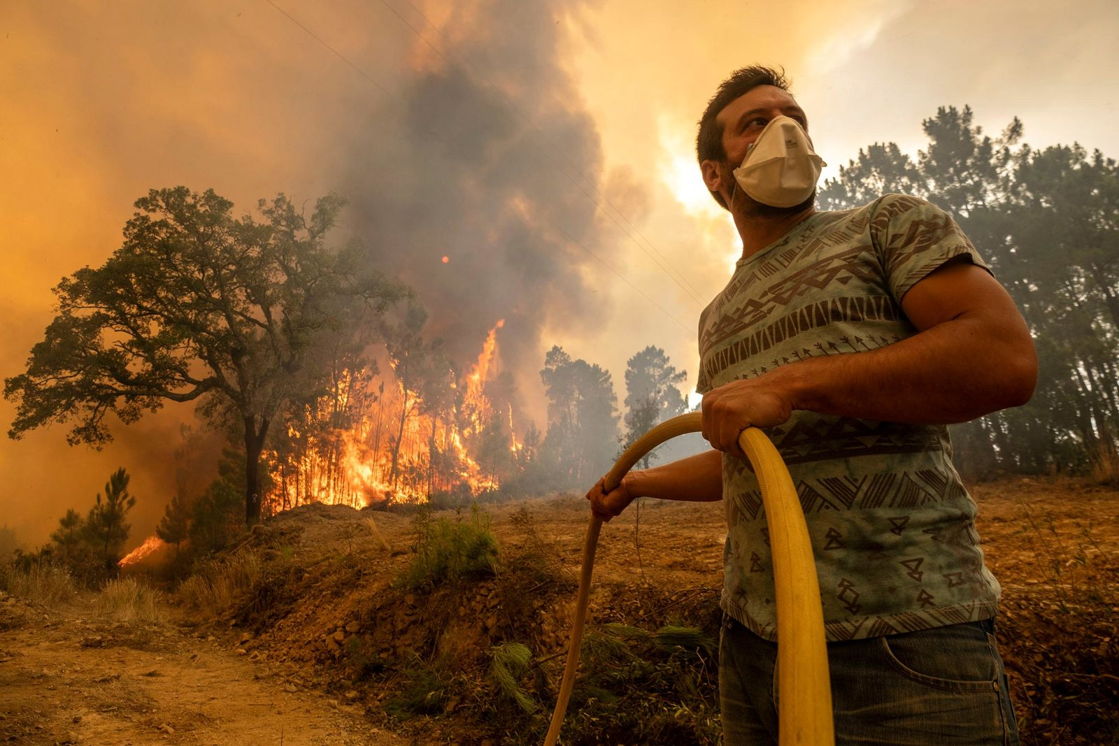 A villager tries to extinguish a wildfire at the village of Chaveira, near Macao, in central Portugal on Monday, July 22, 2019.{ } (AP Photo/Sergio Azenha)