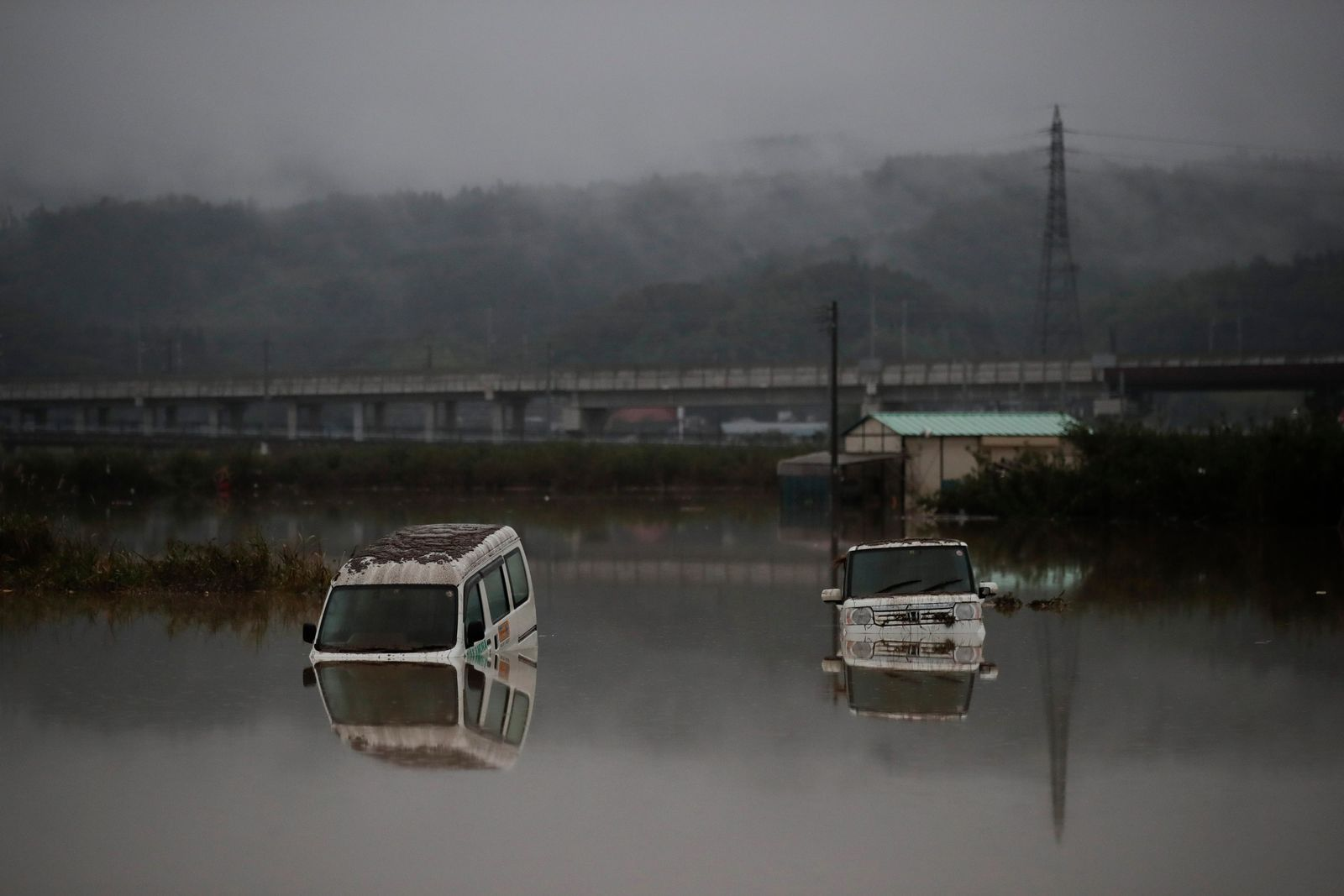 Two vehicles are submerged in floodwaters Monday, Oct. 14, 2019, in Hoyasu, Japan.{ } (AP Photo/Jae C. Hong)
