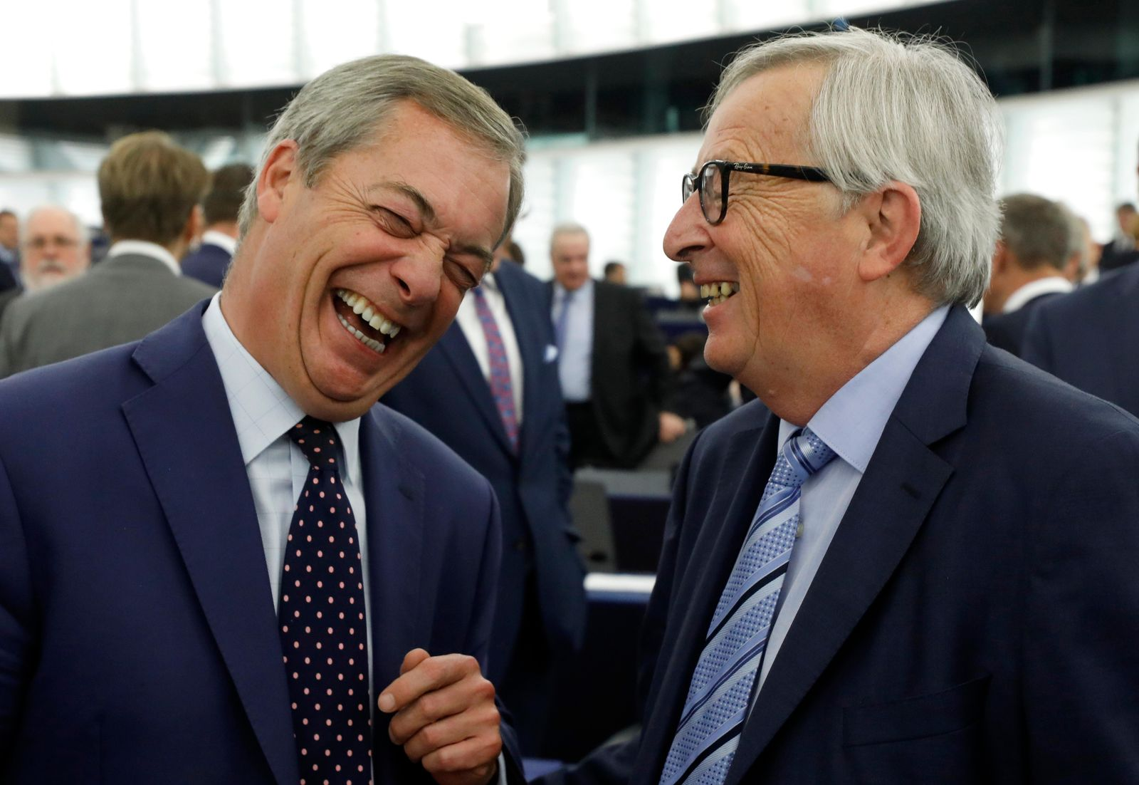 Brexit Party leader Nigel Farage shares a laugh with European Commission President Jean-Claude Juncker Tuesday, Oct. 22, 2019 at the European Parliament in Strasbourg, eastern France. Britain faces another week of political gridlock after British lawmakers on Mond (AP Photo/Jean-Francois Badias)