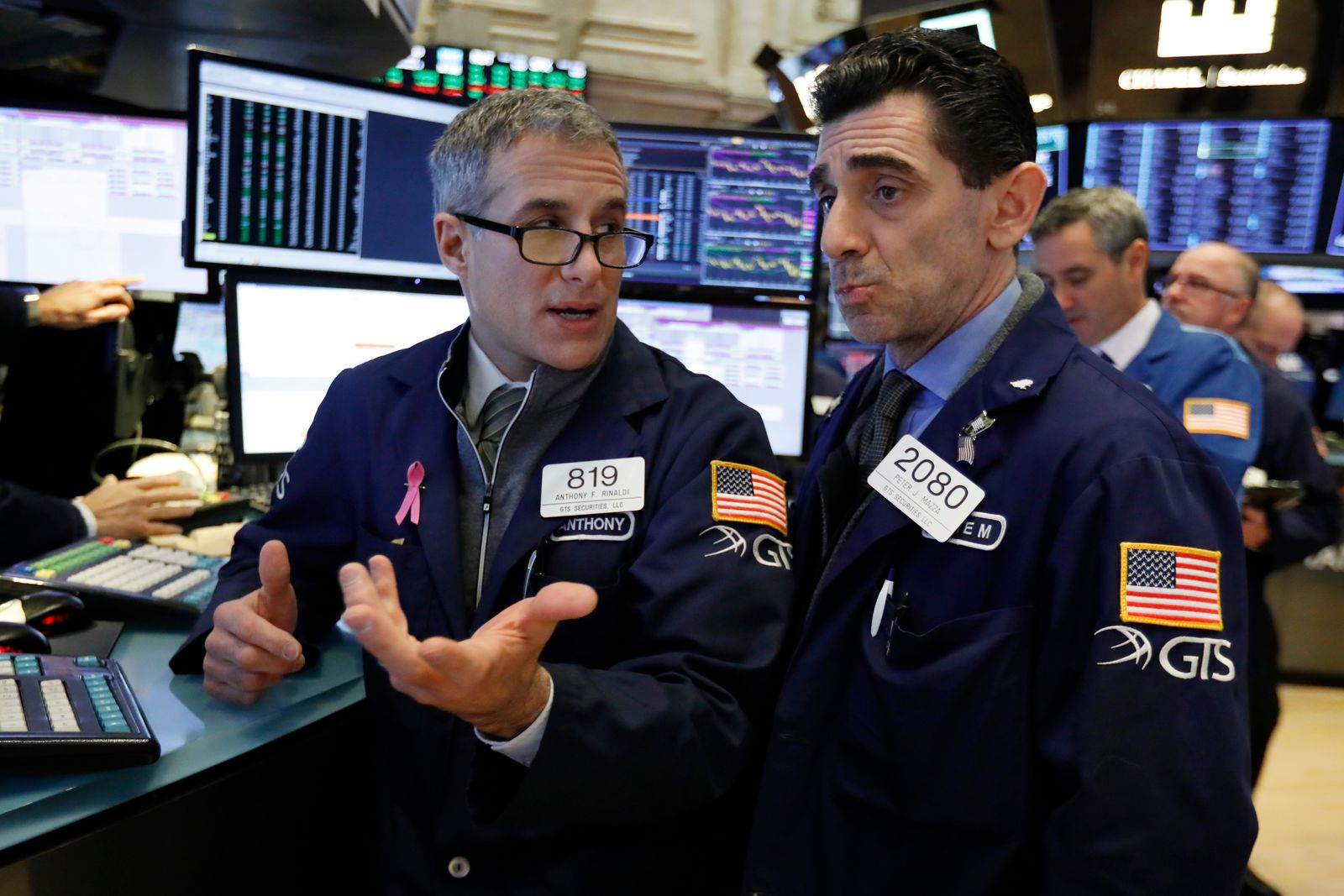 FILE- In this Jan. 4, 2019, file photo specialists Anthony Rinaldi, left, and Peter Mazza confer as they work on the floor of the New York Stock Exchange. (AP Photo/Richard Drew, FIle)