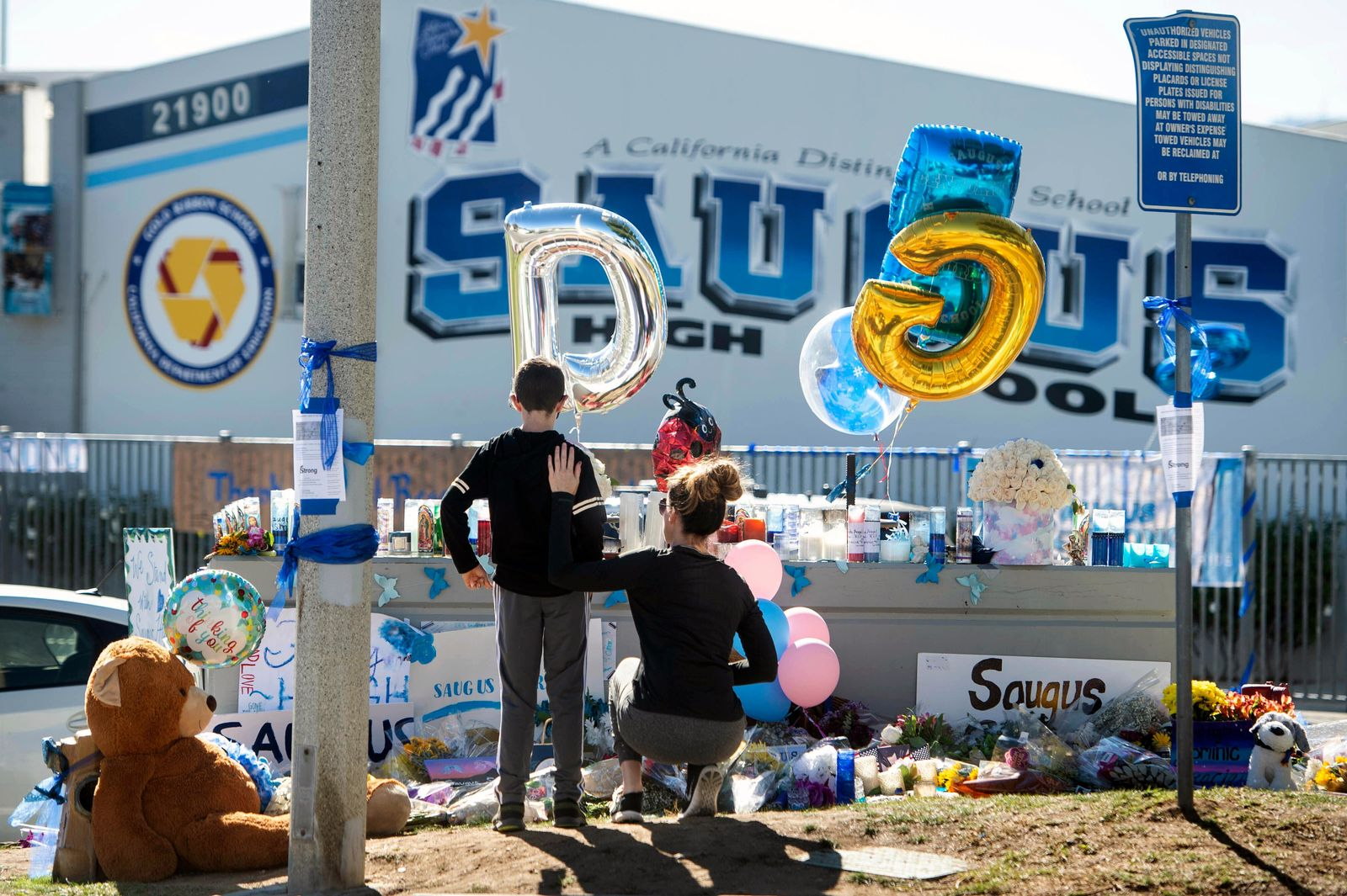 Michelle Bosshard and her 9-year-old son Lucas visit a memorial, Monday, Nov. 18, 2019, for two students killed during a shooting at Saugus High School in Santa Clarita, Calif., days before. The Bosshards, who live in the neighborhood, know a handful of kids who were hiding during the shooting. The students will return to school on Dec. 2. (Sarah Reingewirtz/The Orange County Register via AP)