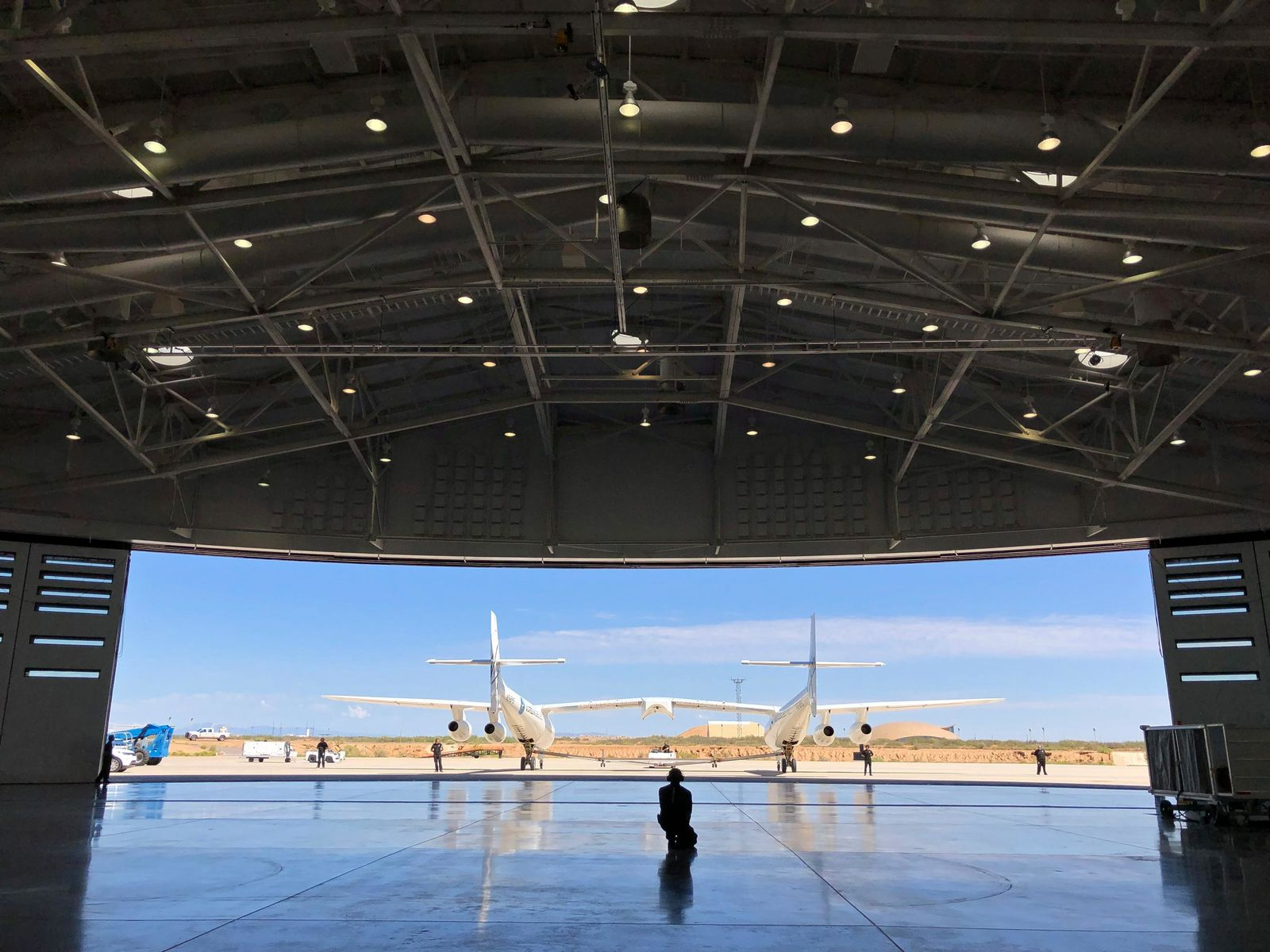 "In this Aug. 15, 2019 file photo, Virgin Galactic ground crew guide the company's carrier plane into the hangar at Spaceport America following a test flight over the desert near Upham, New Mexico. Virgin Galactic is on the verge of making more history in 2020 following an ""incredible"" year of progress, the chief executive of billionaire Richard Branson's space tourism venture said Thursday. (AP Photo/Susan Montoya Bryan, File)"
