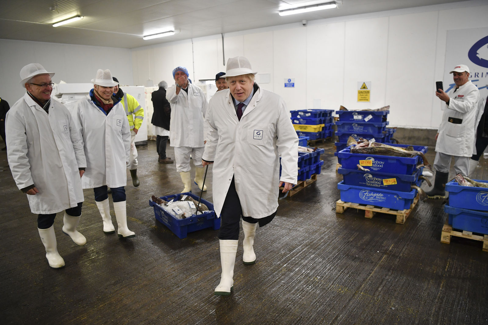 Britain's Prime Minister and Conservative Party leader Boris Johnson, center, visits Grimsby fish market in Grimsby, northeast England, Monday Dec. 9, 2019, ahead of the general election on Dec. 12.{ } (Ben Stansall/Pool via AP)