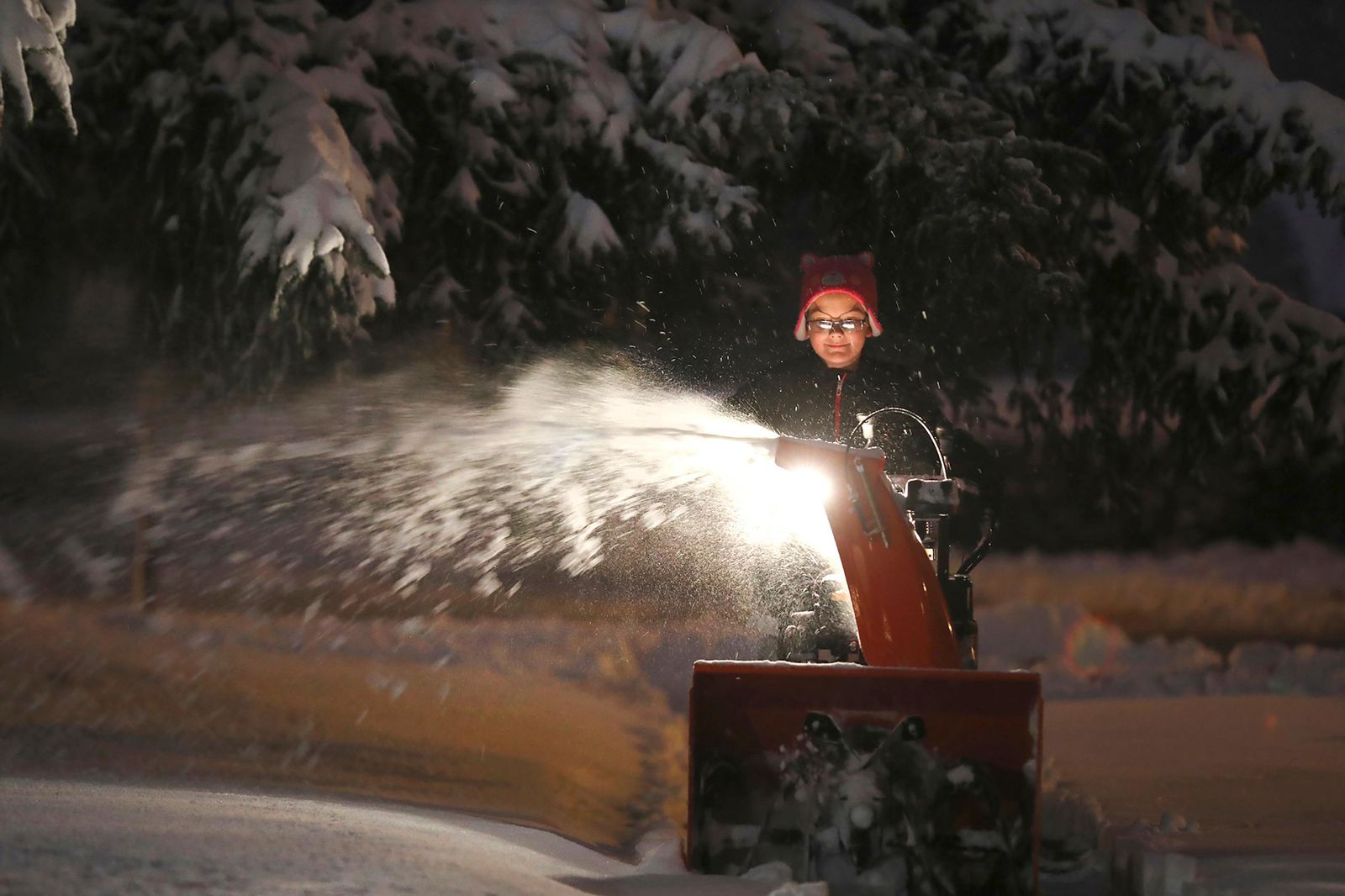 Ryan Corl, 12, uses a snowblower to clear the sidewalk in front of his home Tuesday, Nov. 12, 2019 in Brighton, NY. Western New York is coping with its first major snowstorm of the season. (Tina MacIntyre-Yee/Rochester Democrat and Chronicle via AP)