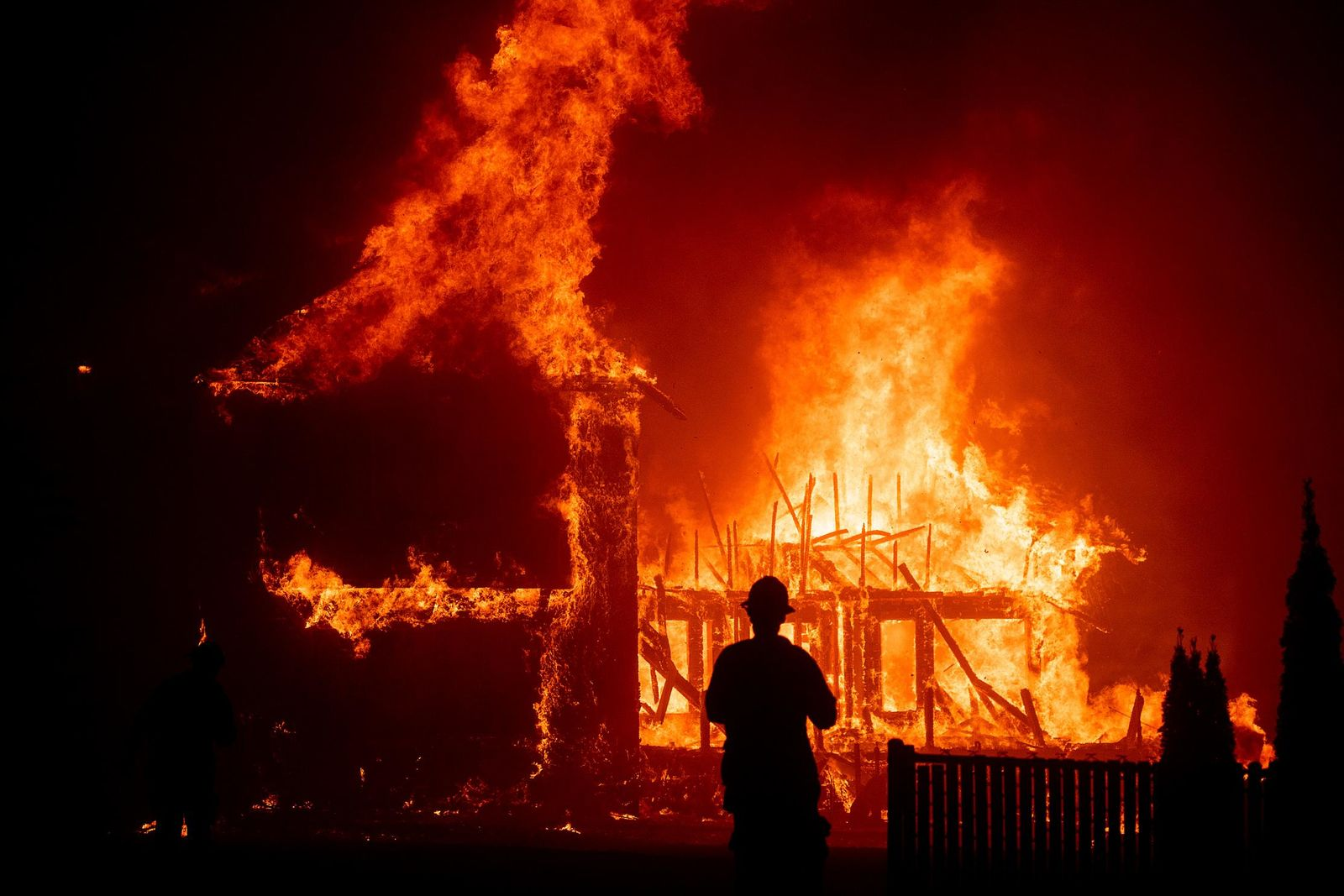 FILE - In this Nov. 8, 2018 file photo, a home burns as a wildfire called the Camp Fire rages through Paradise, Calif.{ } (AP Photo/Noah Berger, File)