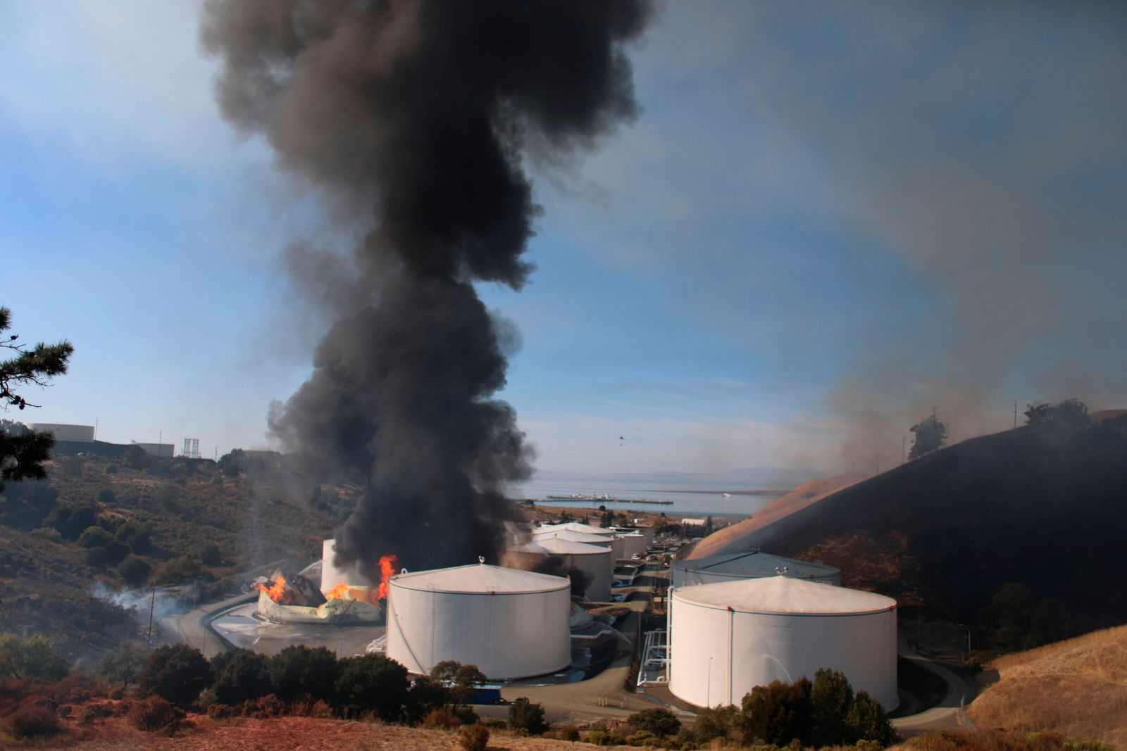 "A fire broke out at NuStar Energy LP facility in Crockett, Calif., Tuesday, Oct. 15, 2019. The Contra Costa Health Department posted on Twitter that there was a ""hazardous materials emergency"" in the towns of Crockett, and Rodeo. The department urged residents to stay inside and close all windows and doors. (Anda Chu/San Jose Mercury News via AP)"