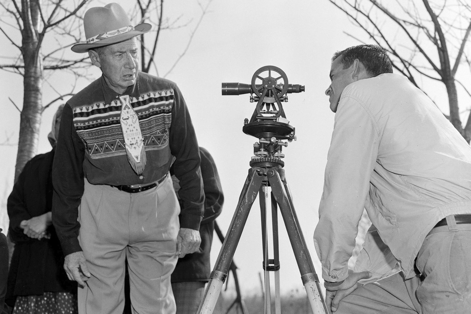 FILE - In this April 18, 1958 file photo, Philip N. Brooks, right, a New York State surveyor, takes a look through his transit on the Tuscarora Indian Reservation near Niagara Falls, N.Y., while Tuscarora Chief Elton Black Cloud Greene watches. The tribe is resisting state seizure of their land for a power project. In 1959, the U.S. government started the switch from the U.S. survey foot to the international foot, and it will finish the job in 2022. (AP Photo)