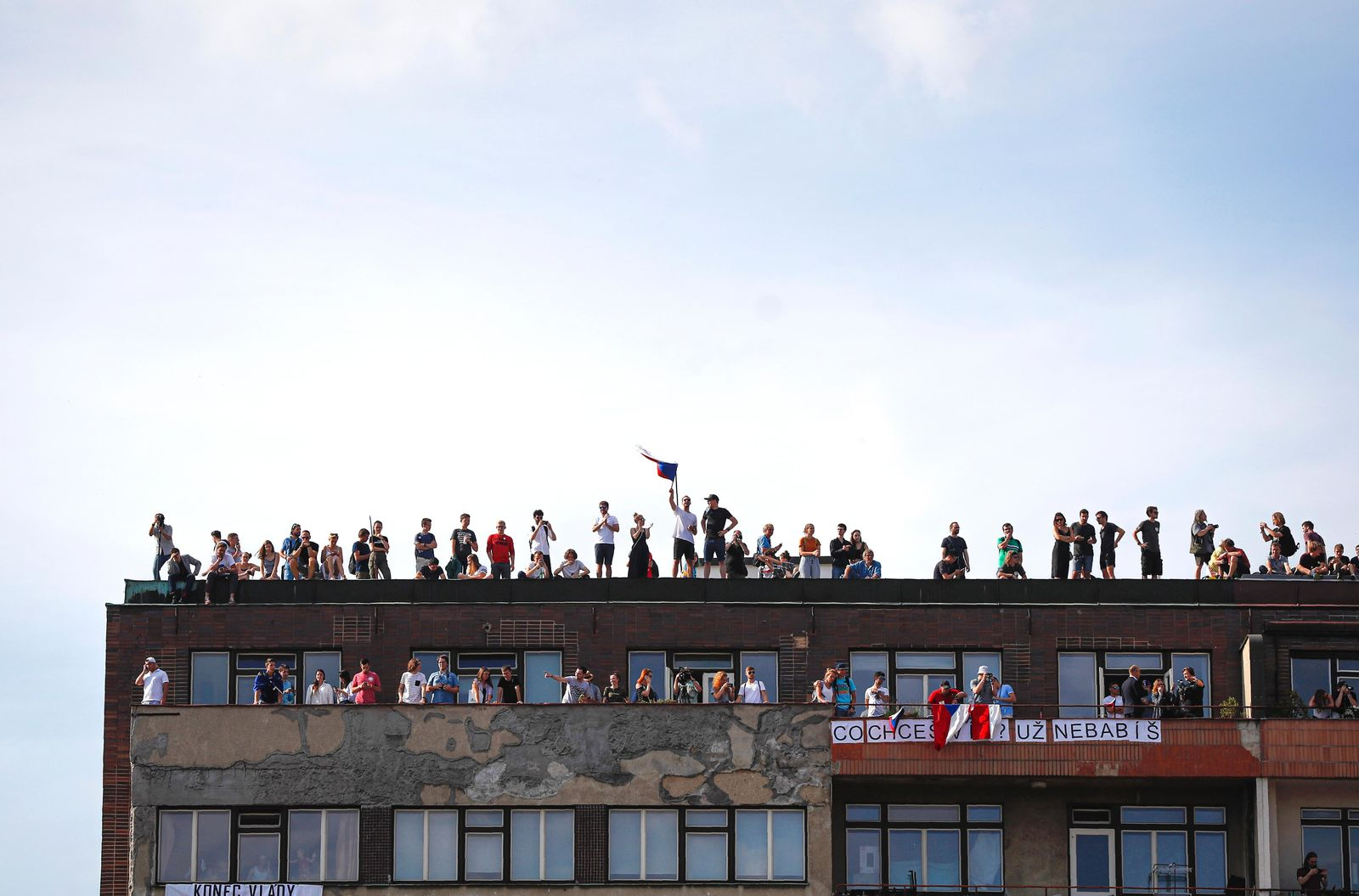 People watch from a nearby building as protesters demand the resignation of Czech Prime Minister Andrej Babis in Prague, Czech Republic, Sunday, June 23, 2019. Protesters are on calling on Czech Prime Minister Andrej Babis to step down over fraud allegations and subsidies paid to his former companies. (AP Photo/Petr David Josek)