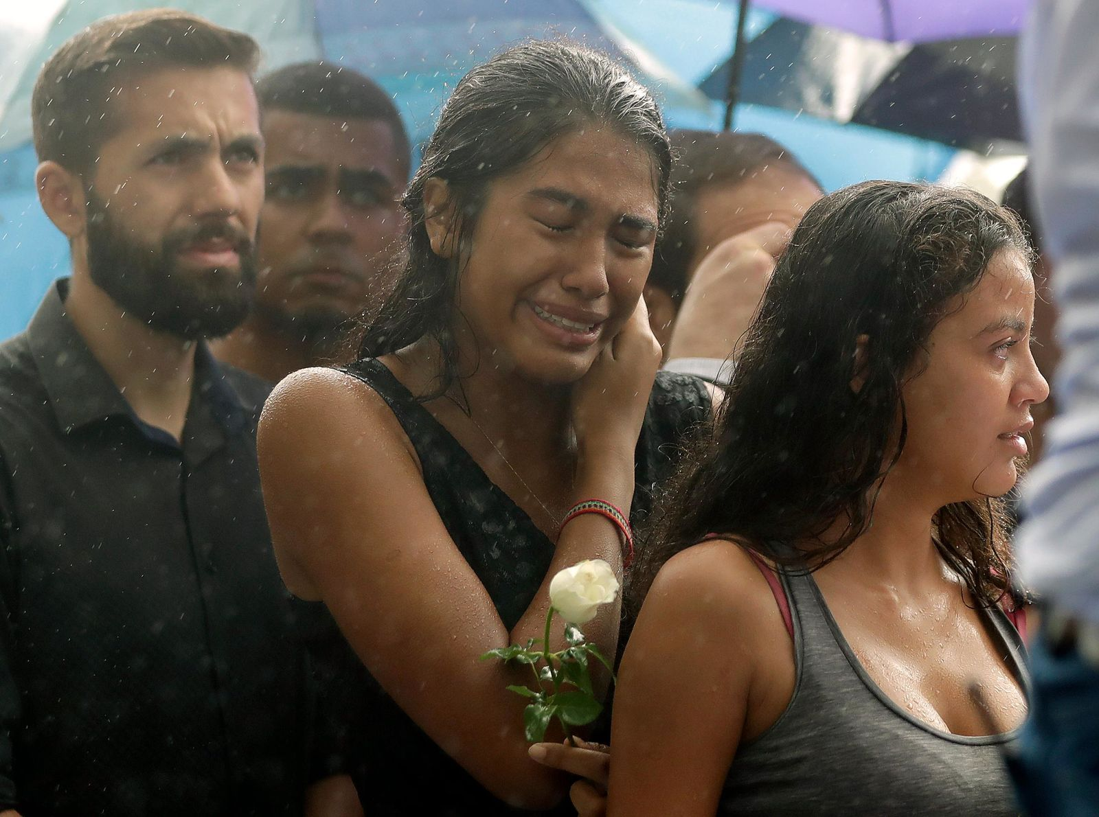A woman stands weeping in the rain during the burial of 15-year-old student Kaio Lucas da Costa Limeira, a victim of a mass shooting at the Raul Brasil State School in Suzano, Brazil, Thursday, March 14, 2019. (AP Photo/Andre Penner)