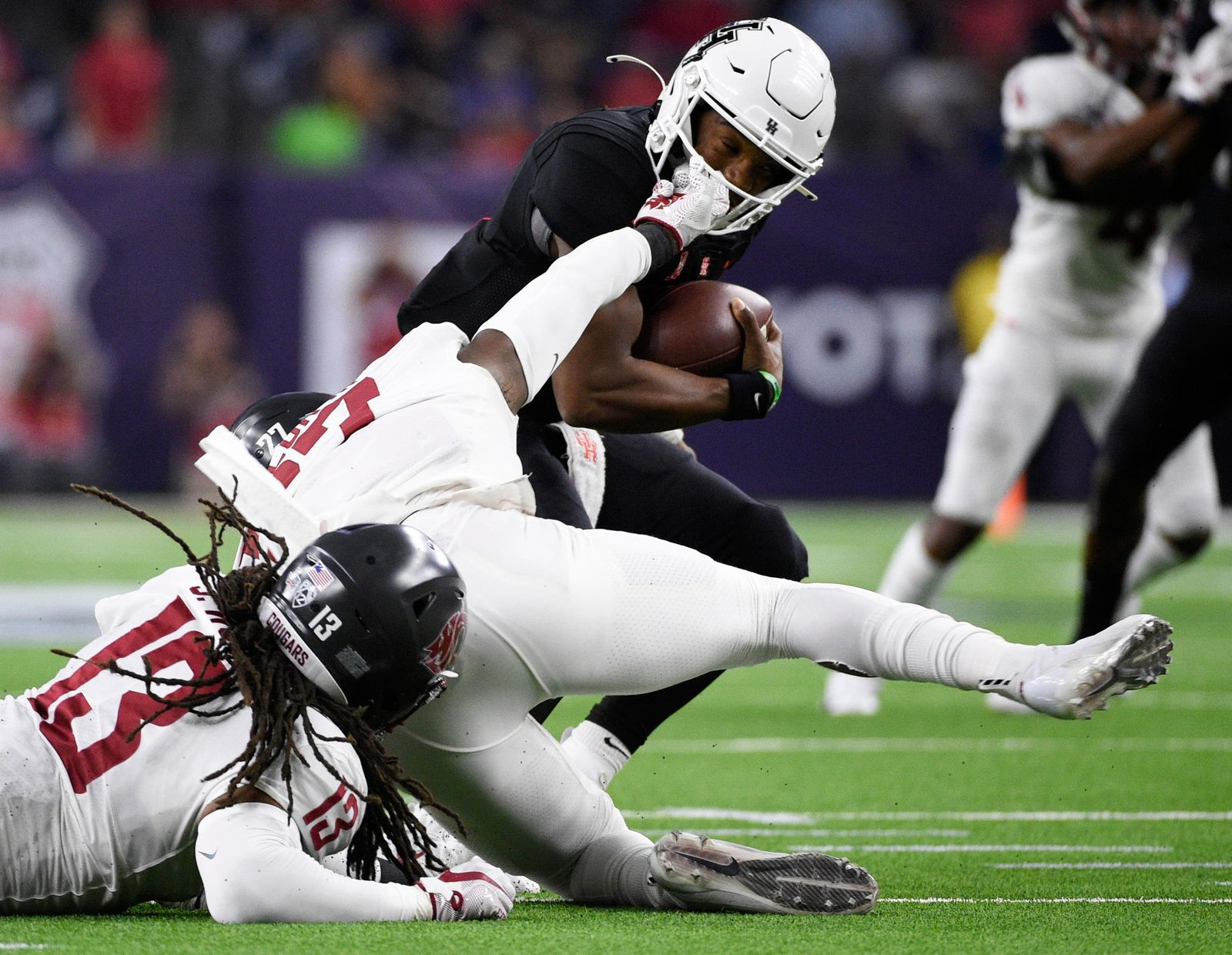 Houston quarterback D'Eriq King, top, escapes the sack attempt of Washington State's Willie Taylor III (27) during the first half of an NCAA college football game Friday, Sept. 13, 2019, in Houston. (AP Photo/Eric Christian Smith)
