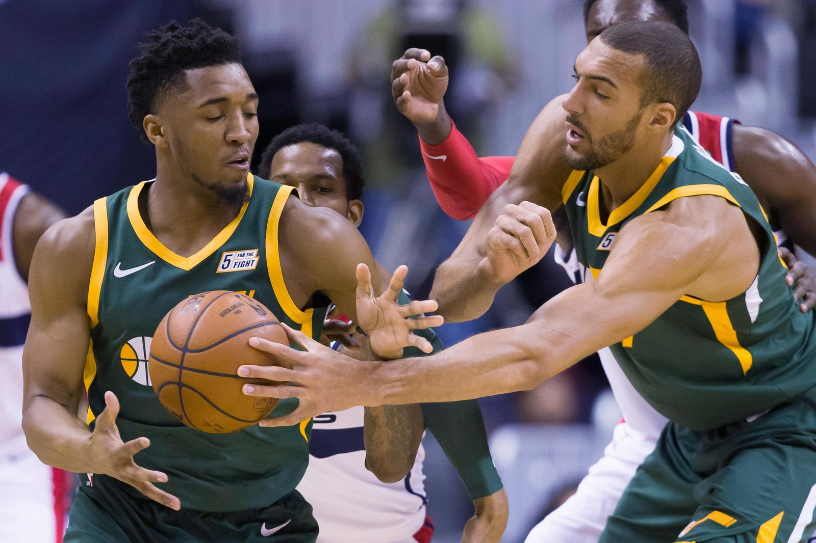 Utah Jazz guard Donovan Mitchell, left, gets the ball from center Rudy Gobert (27), from France, with Washington Wizards forward Trevor Ariza, back left, defending during the first half of an NBA basketball game Monday, March 18, 2019, in Washington. (AP Photo/Alex Brandon)