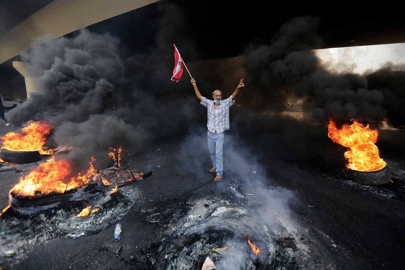 An anti-government protester makes victory sign, as he holds a Lebanese national flag and walks fire of tires that sits to block a road during a protest against government's plans to impose new taxes in Beirut, Lebanon, Friday, Oct. 18, 2019. (AP Photo/Hassan Ammar)