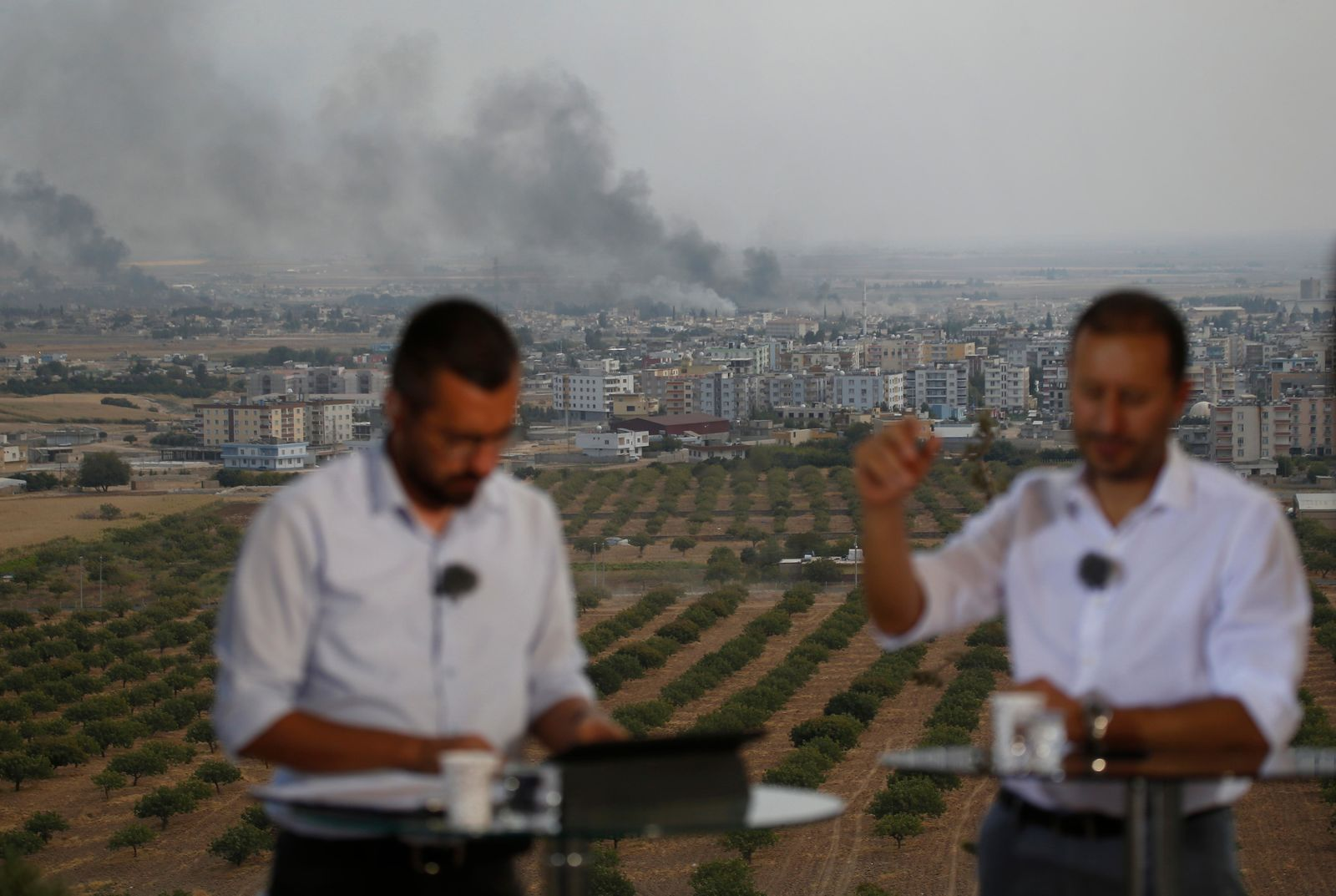 TV journalists talk during a live broadcast on a hilltop in Ceylanpinar, Sanliurfa province, southeastern Turkey, as in the background smoke billows from targets in Ras al-Ayn, Syria, during bombardment by Turkish forces, Wednesday, Oct. 16, 2019. Turkey's President Recep Tayyip Erdogan called Wednesday on Syrian Kurdish fighters to leave a designated border area in northeast Syria 'as of tonight' for Turkey to stop its military offensive, defying pressure on him to call a ceasefire and halt its incursion into Syria, now into its eighth day.(AP Photo/Lefteris Pitarakis)