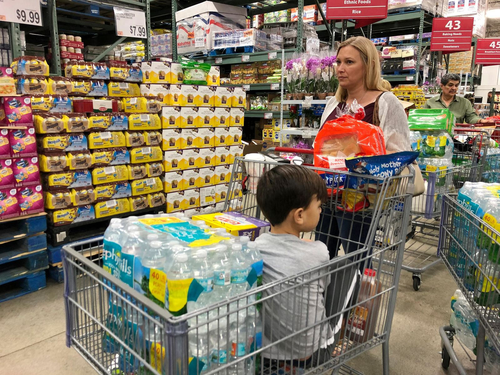 Tiffany Miranda of Miami Springs stands in line with supplies at a BJ's Wholesale Club Thursday, Aug. 29, 2019, in Hialeah, Fla.{ } (AP Photo/Marcus Lim)