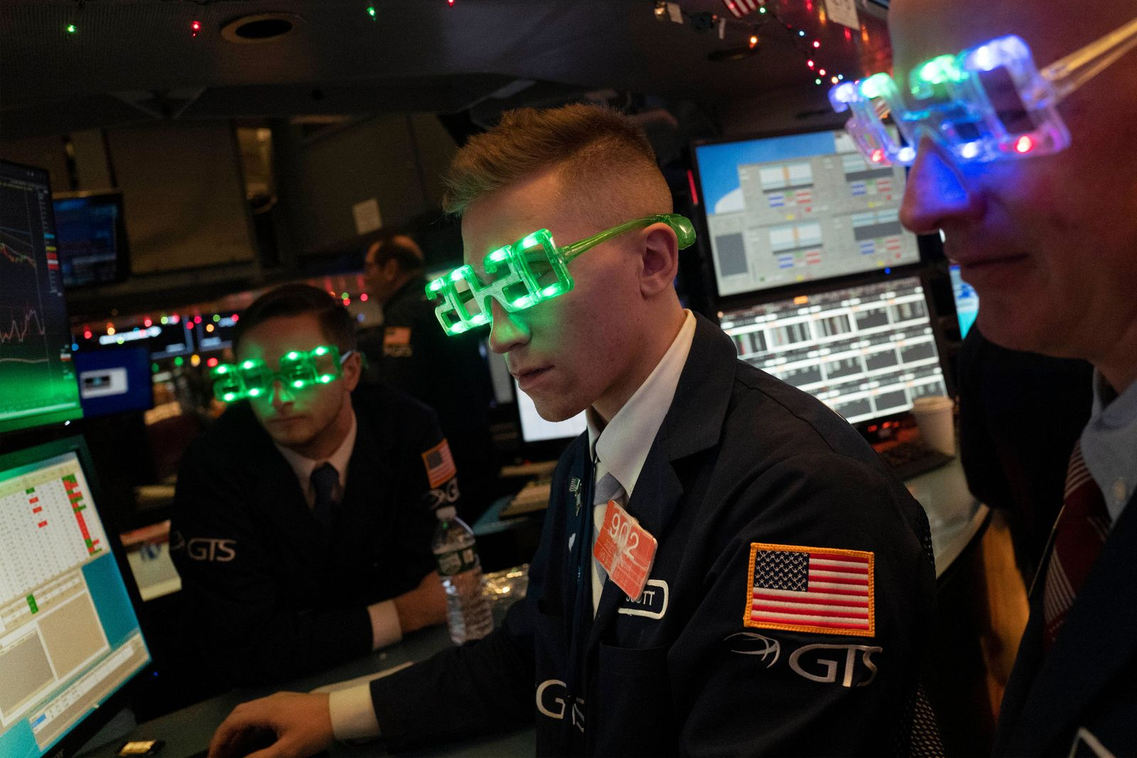 Stock traders wear New Year's 2020 party glasses at New York Stock Exchange, Tuesday, Dec. 31, 2019. Stocks slipped globally in quiet New Year's Eve trading Tuesday with many markets closed. Wall Street could close 2019 with back-to-back daily losses in a year that the U.S. posted the largest market gains since 2013. (AP Photo/Mark Lennihan)