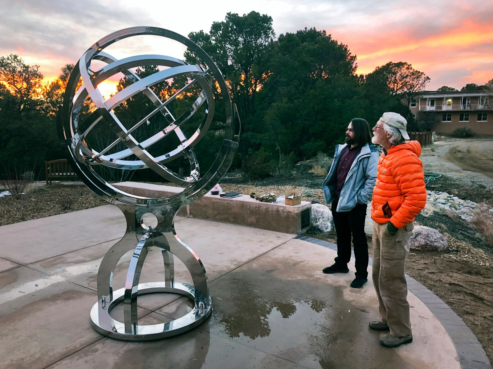 In this Dec. 11, 2019 photo Bill Donahue, right, a retired teacher and director of laboratories at St. John's College, and student Devin Ketch use an armillary sphere to track planetary rotations and explore the history of astronomy in Santa Fe, N.M. The unique precision-steel replica of an instrument created by Danish astonomer Tycho Brahe was commissioned by graduates of the college where students trace the evolution of math and science from early civilizations. (AP Photo/Morgan Lee)